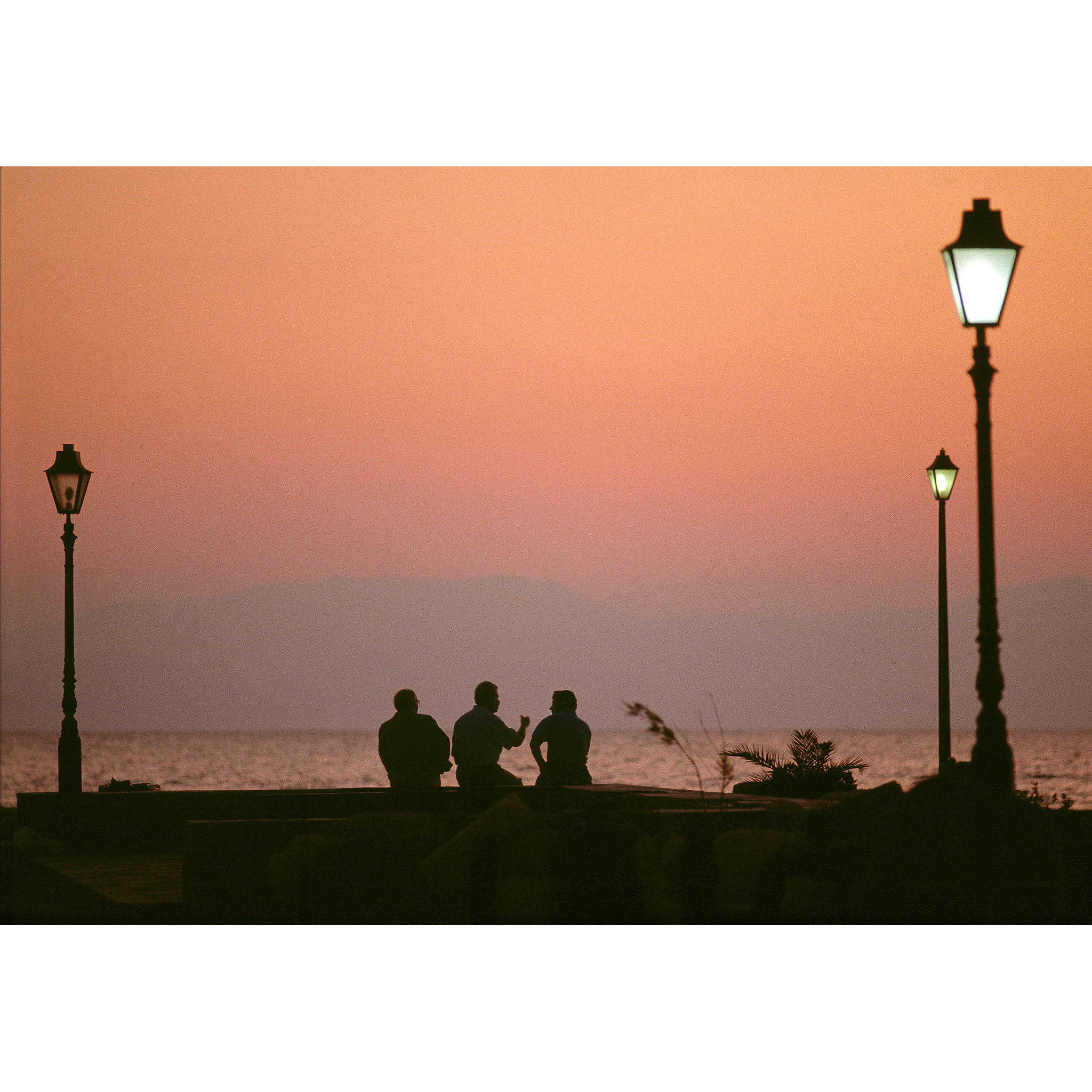 Greek men at sunset overlooking water photograph