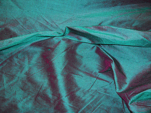 """Iridescent Fabric-  Iridescent fabrics appear to change color depending upon the angle of view and lighting conditions. This effect is caused by weaving with one color in the """"warp"""" and another in the """"weft"""". Most of our iridescent fabrics are shimmery, lustrous, bold, and beautiful."""