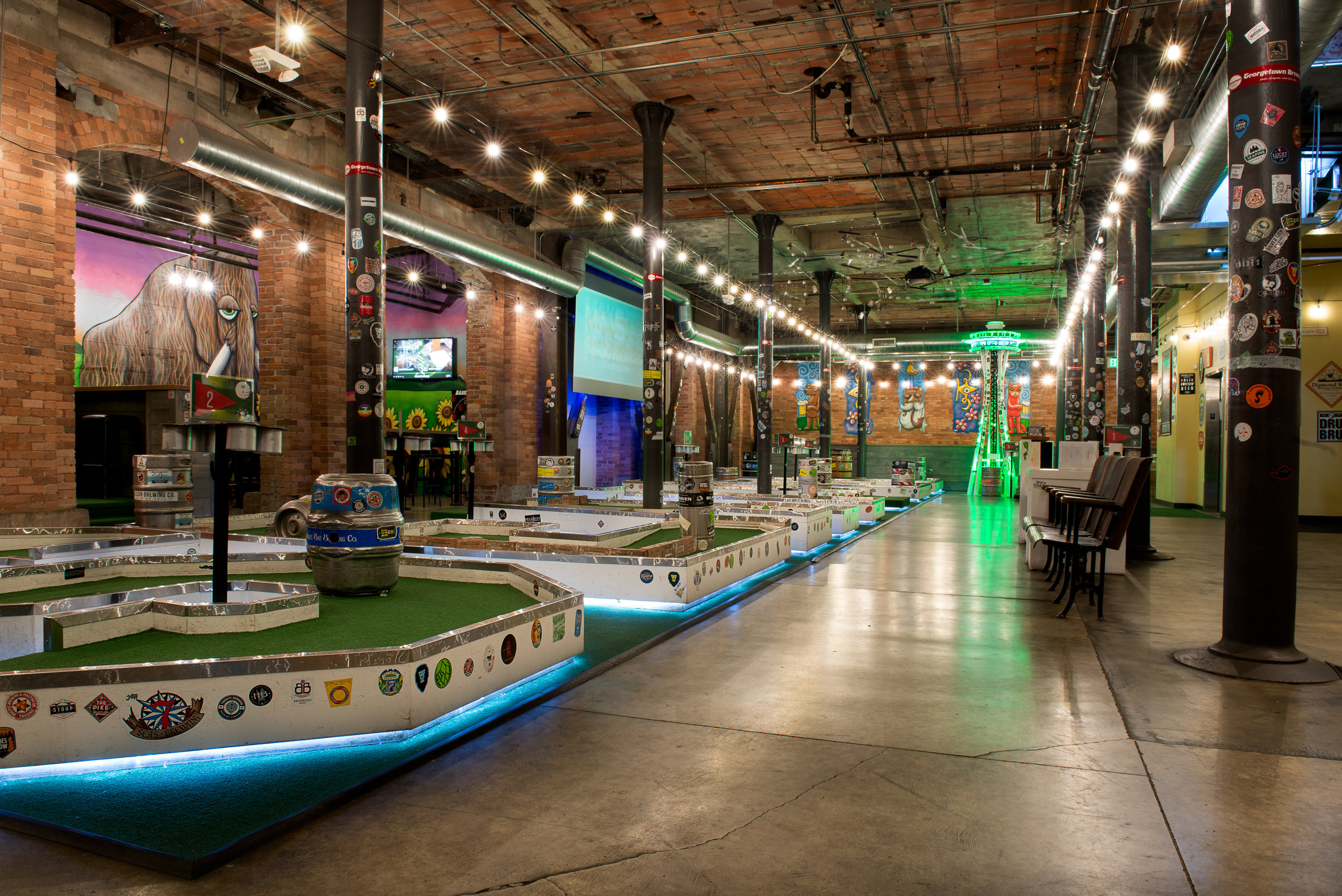 ABOVE: The miniature golf room with historic columns and high ceilings that was previously an electrical substation.  BELOW: Semi-private party rooms surround the miniature golf area and give new life to historic areaways below the sidewalk.