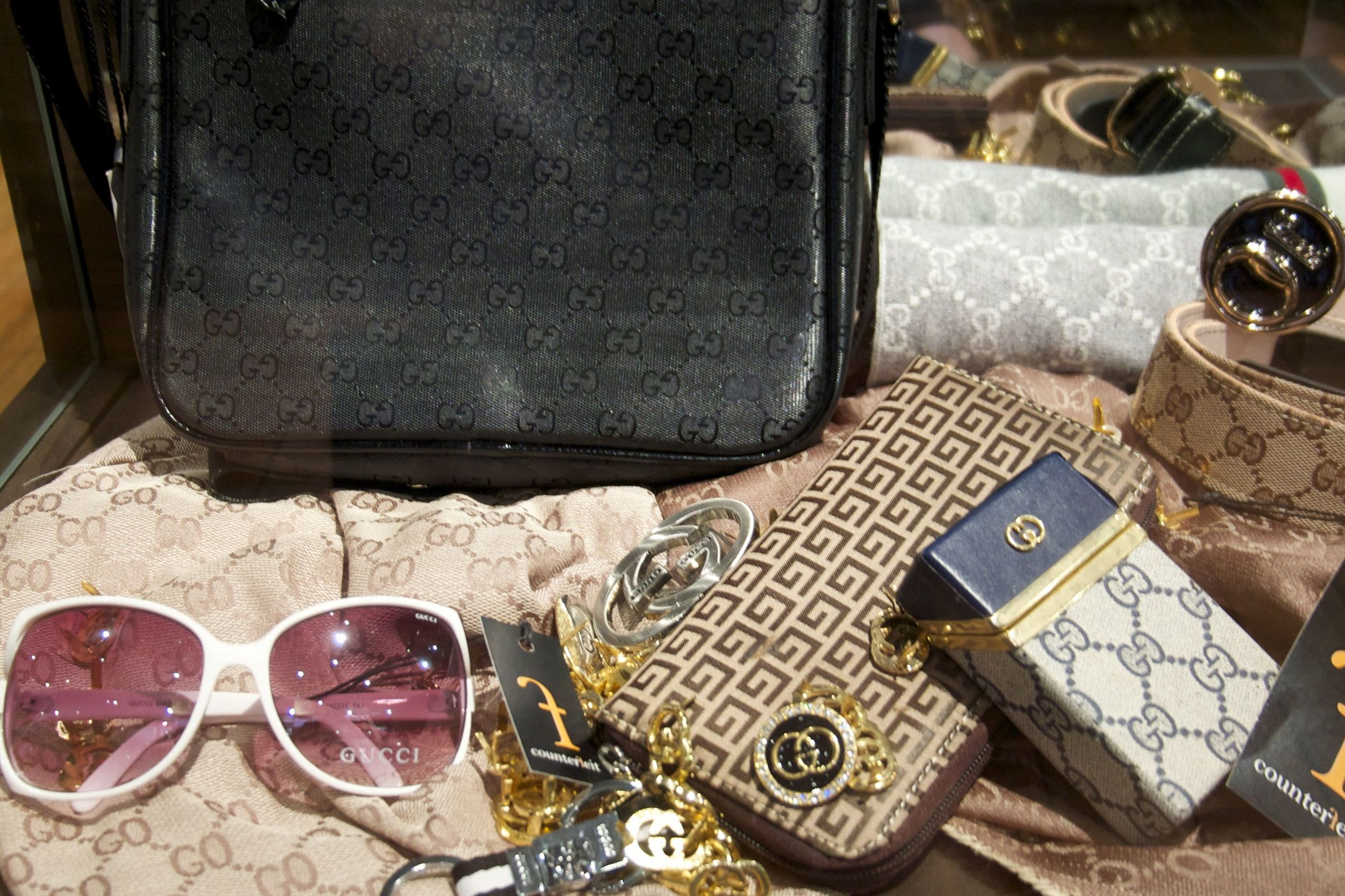 G is For Fake: Counterfeit Gucci merchandise, including sunglasses, belts, and earrings.