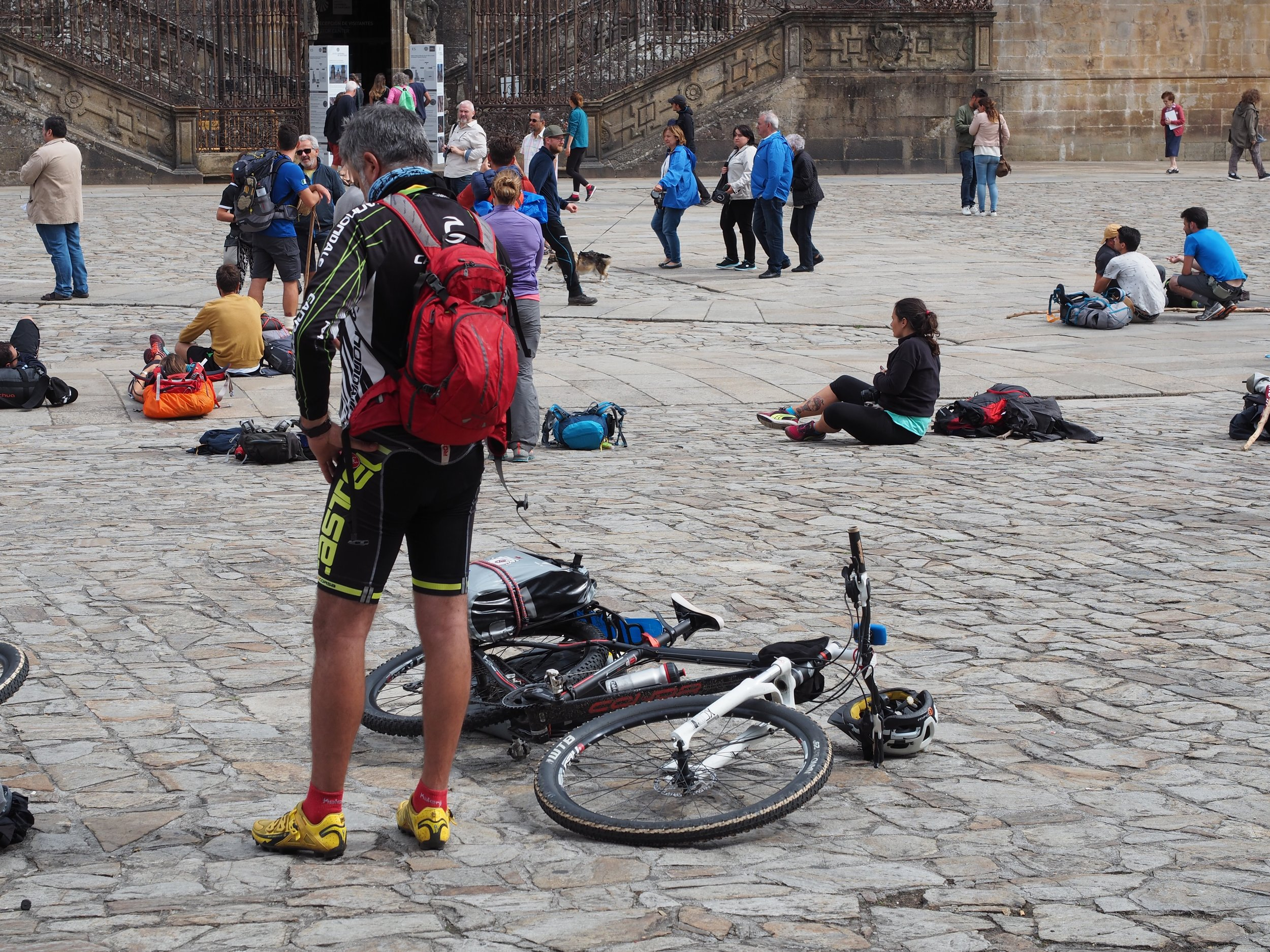 Tired cyclist arrives at the Cathedral of Santiago