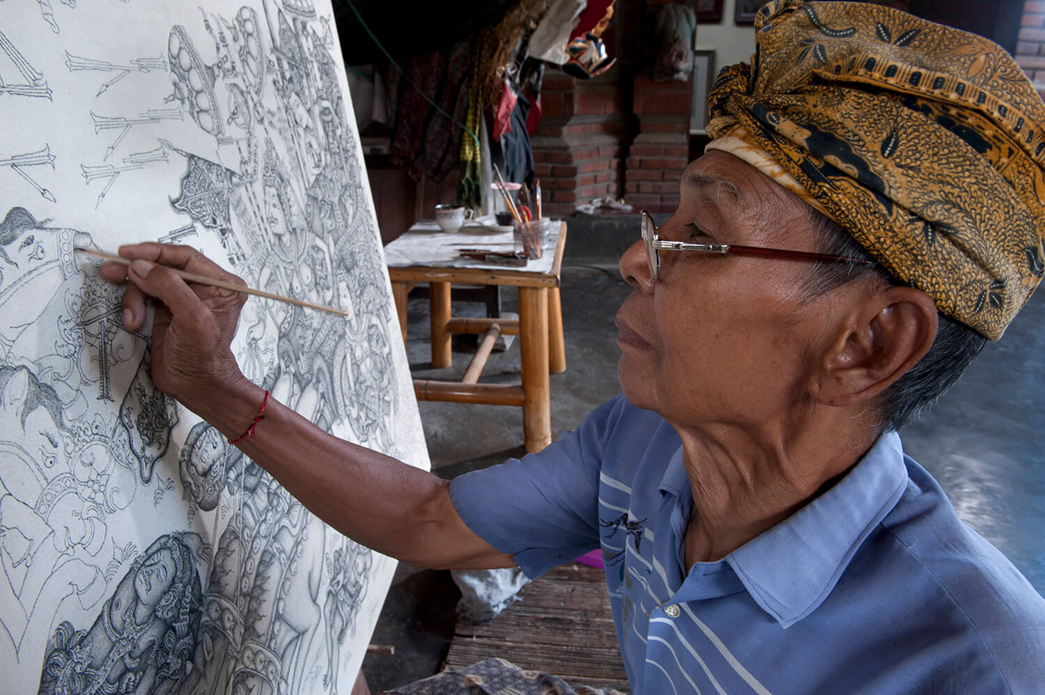 Ketut Madra in April 2013 inking a detail of a Mahabharata painting