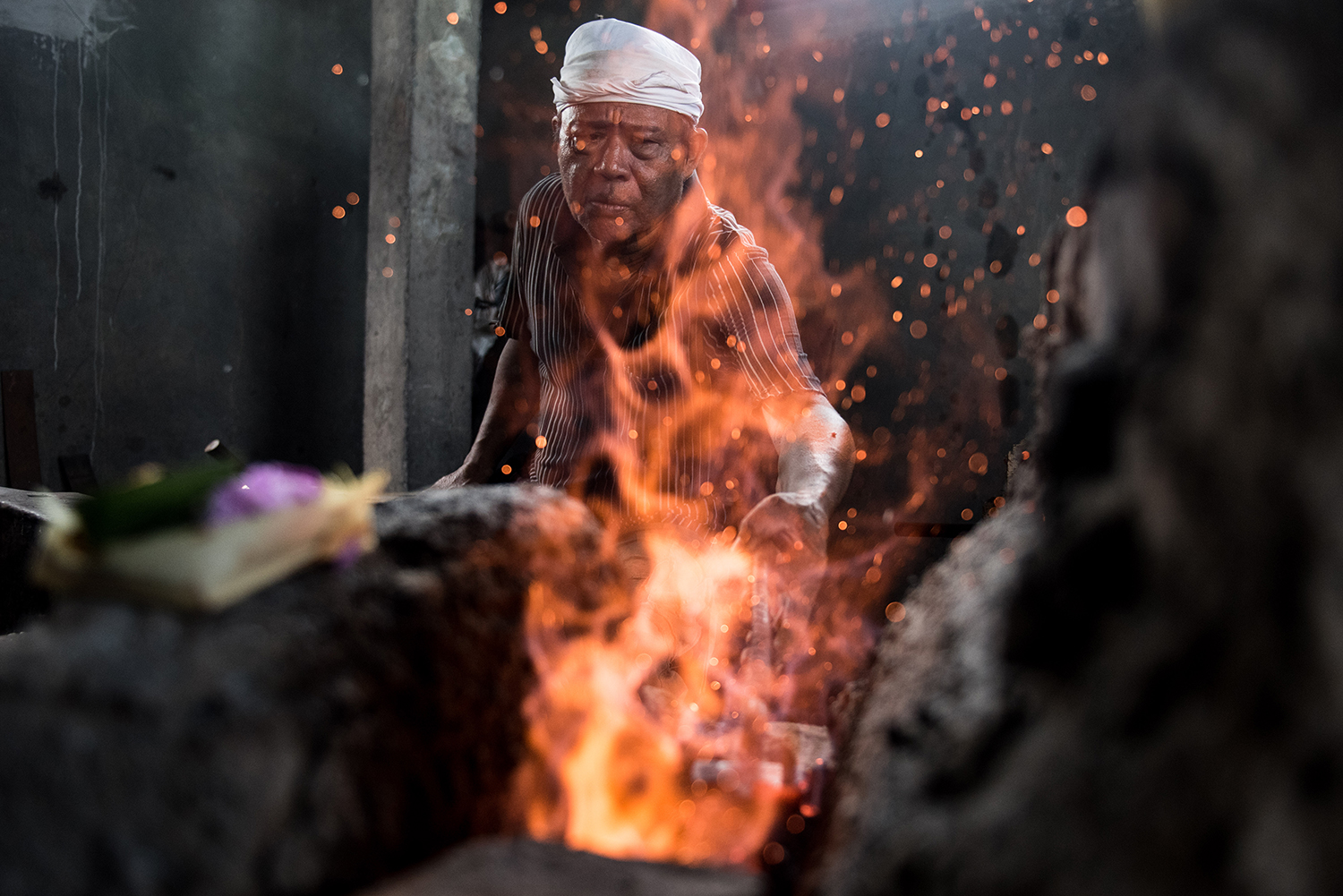 Pandé Ketut Mudra of Kusambe reaches into his forge with a tool to examine the readiness of a knife blade he is forging.