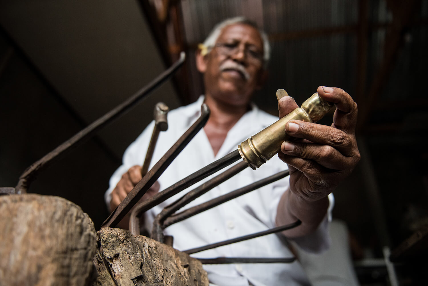 In the initial stage, using traditional tools for  repoussé metalwork, he begins to shape a figurine handle.