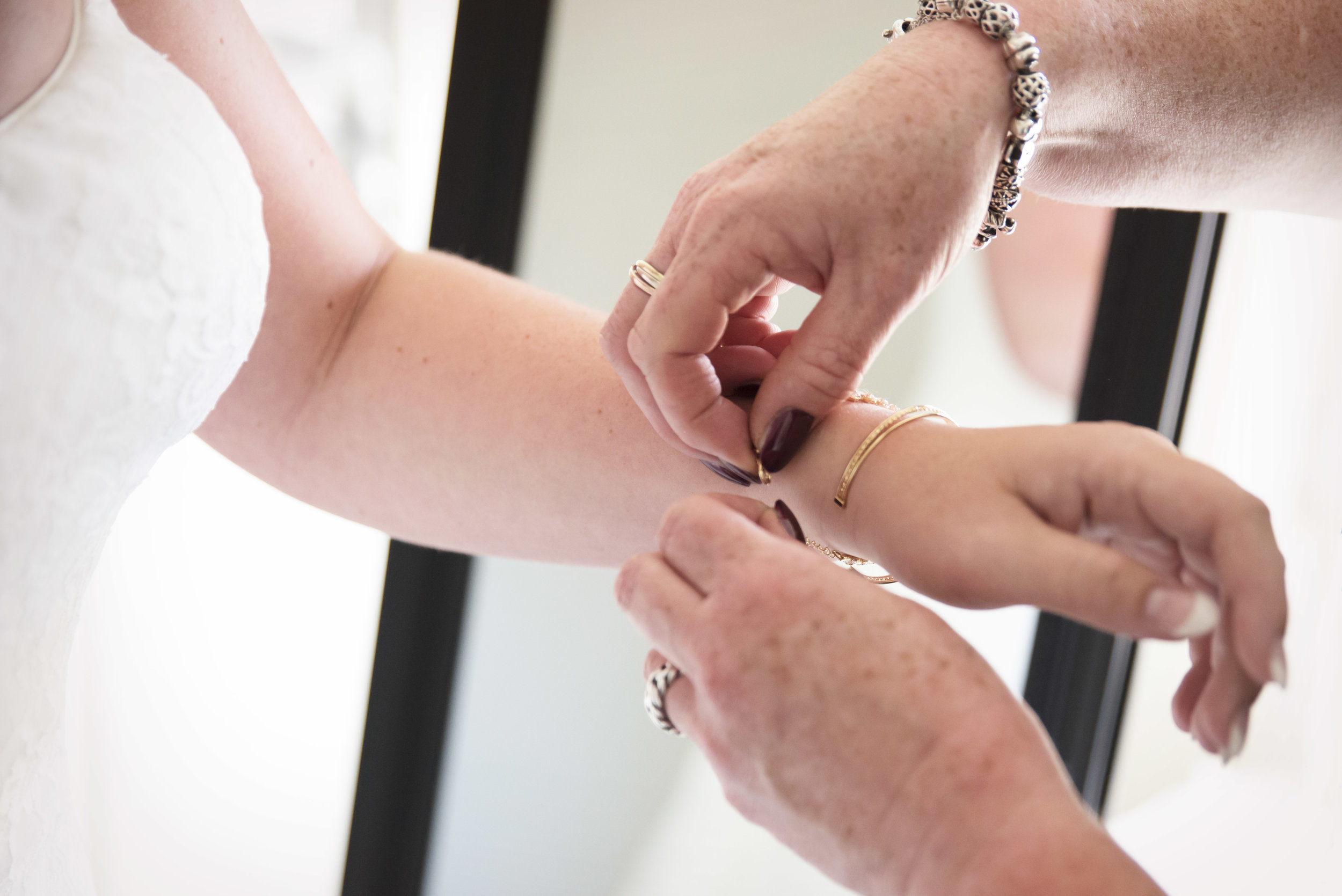 de moeder van de bruid hielp met het aandoen van de sieraden van de bruid