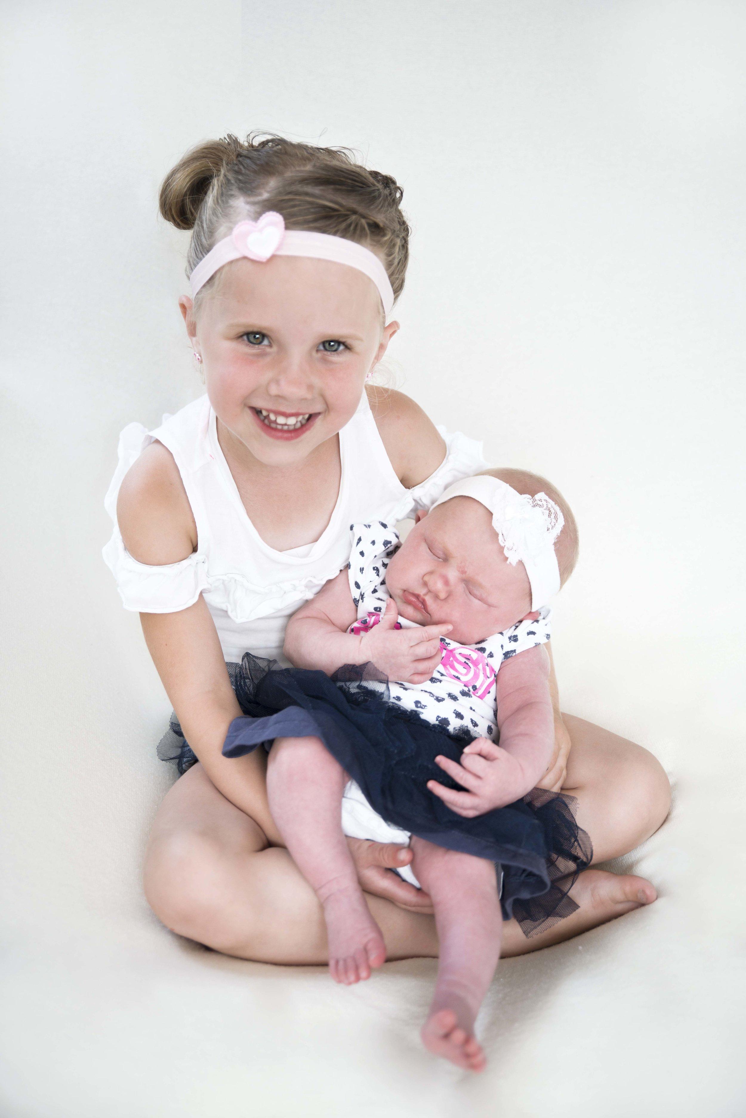 babyfoto bij zus op schoot