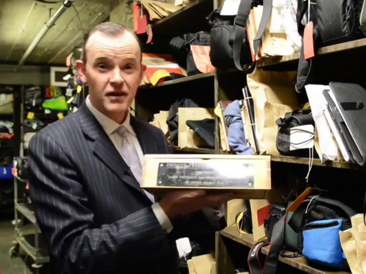 Paul Cowan holds up the box containing the ashes of Thomas Frederick Johnston. Source London Live.
