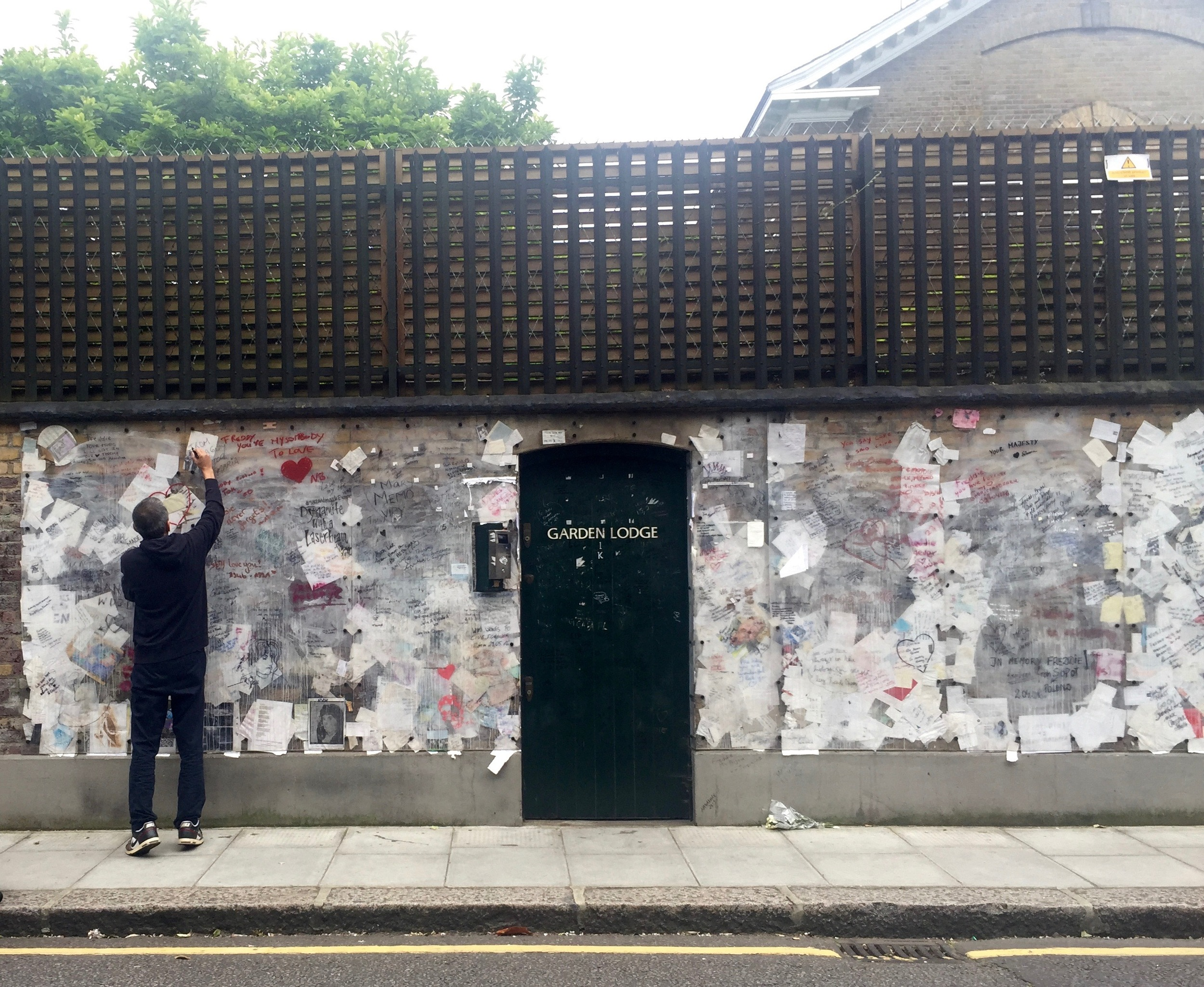 Signing the wall at 1 Logan Place, Kensington. Former home of Freddie Mercury.