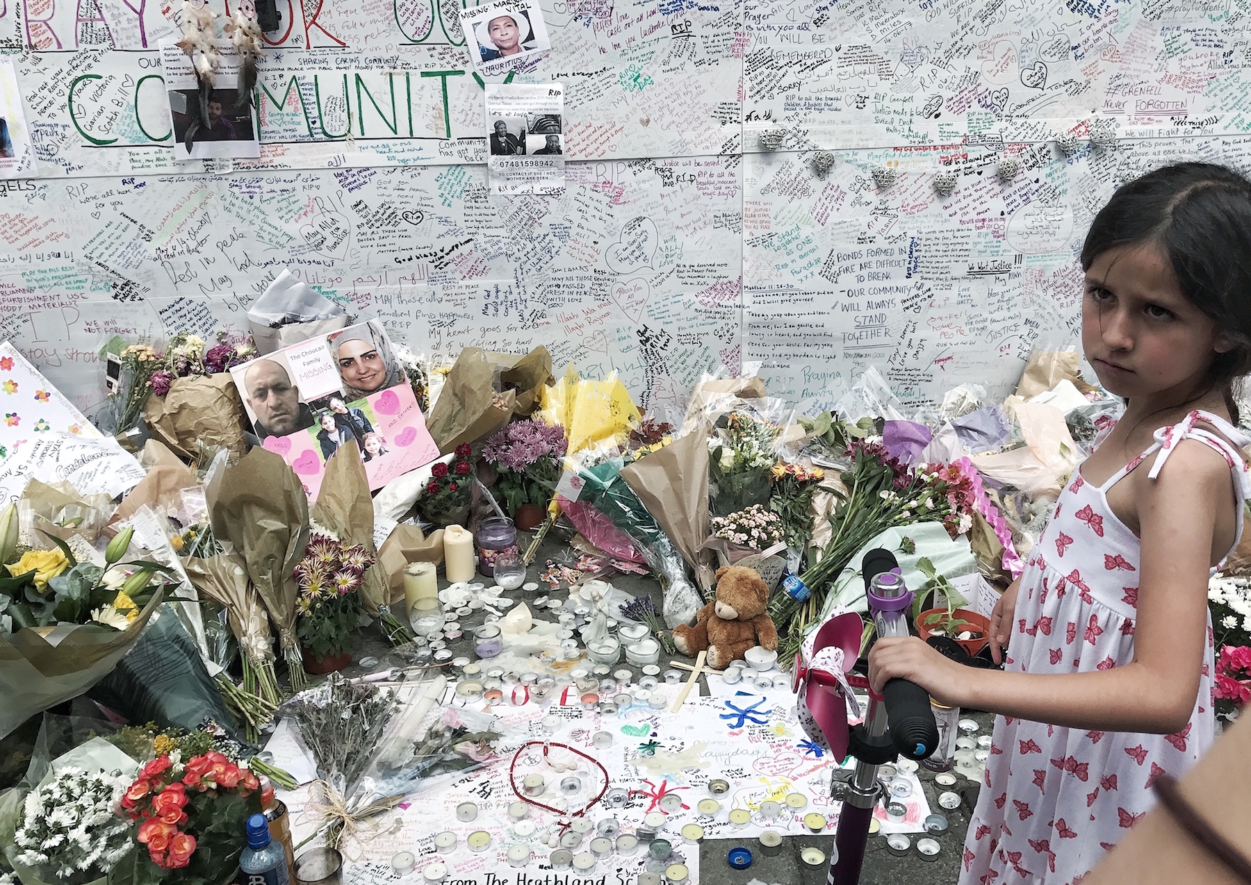 Little Girl looks on as people look for signs that there loved ones are still alive. Grenfell Tower fire. London