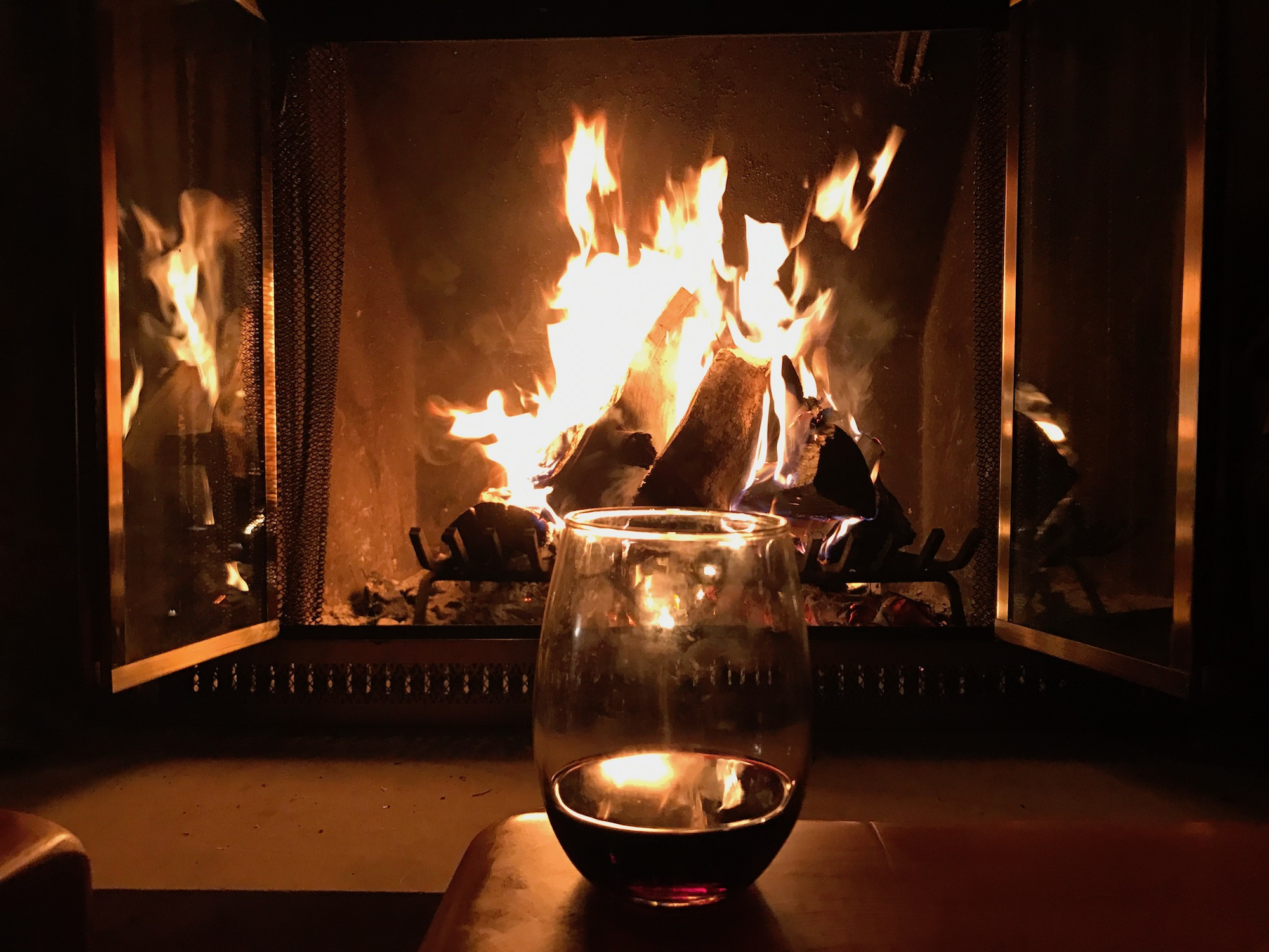 Fire at the ski chalet with glass of wine.jpeg