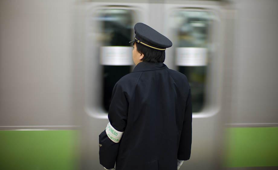 A conductor waits as a Yamanote Train passes at Shibuya Station