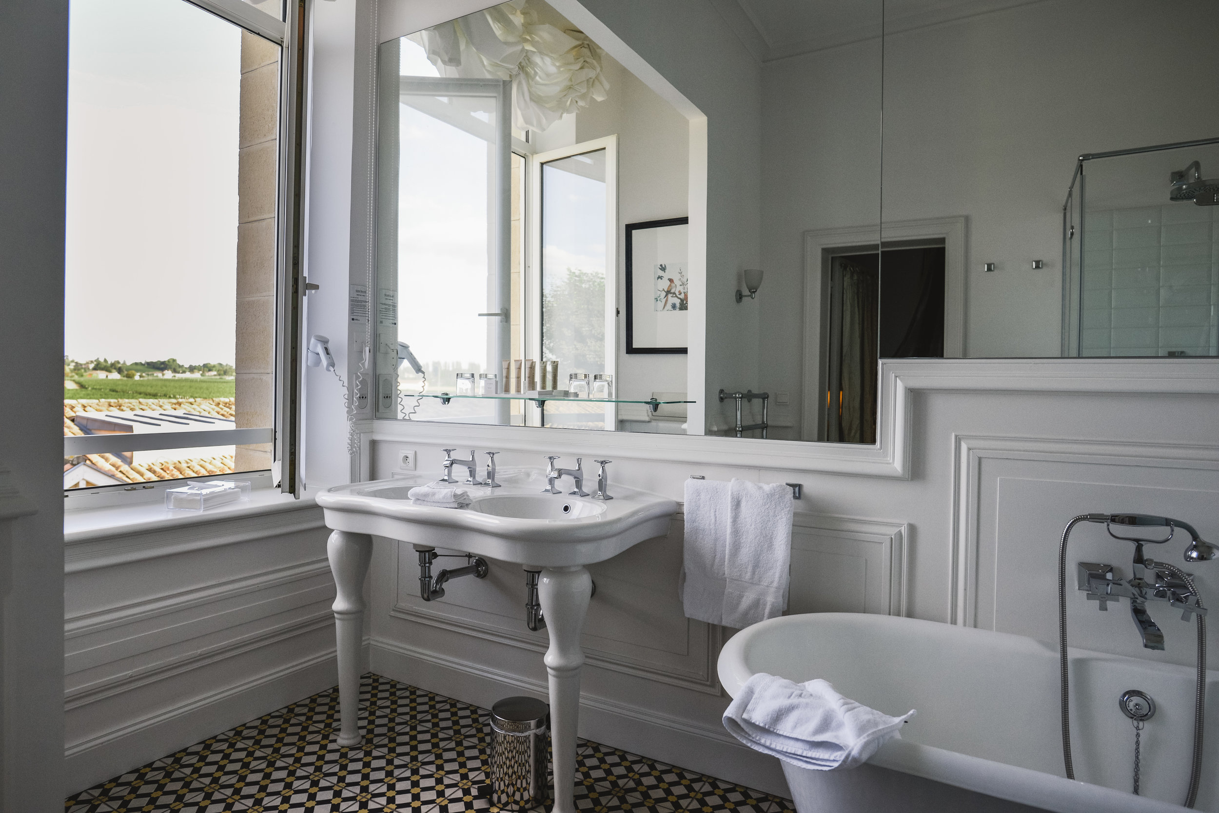 The fabulously classic bathroom in our chateau suite - complete with artisan tile flooring and a chic claw-foot tub.