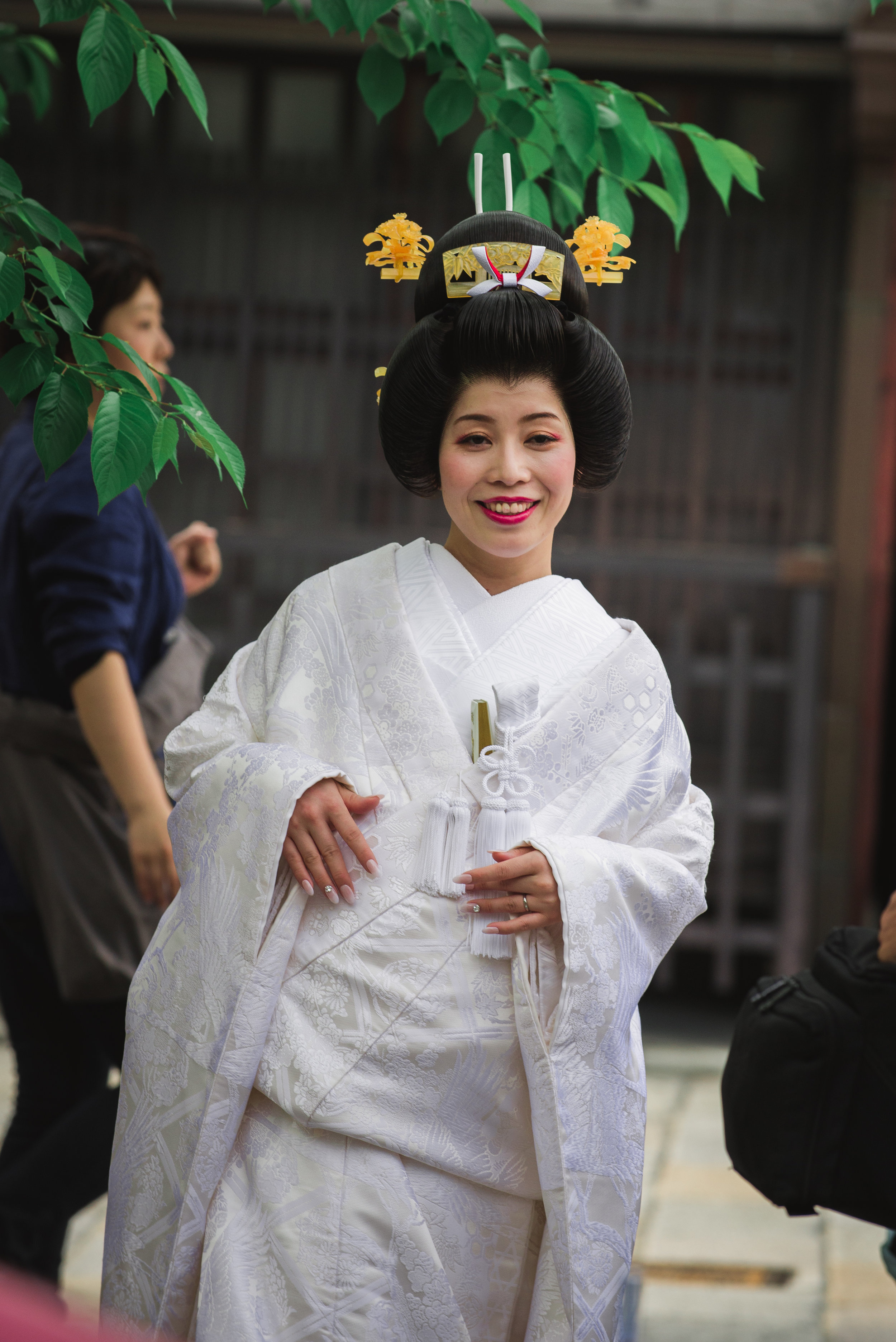 A woman dressed in a bridal kimono for a photo shoot in the city