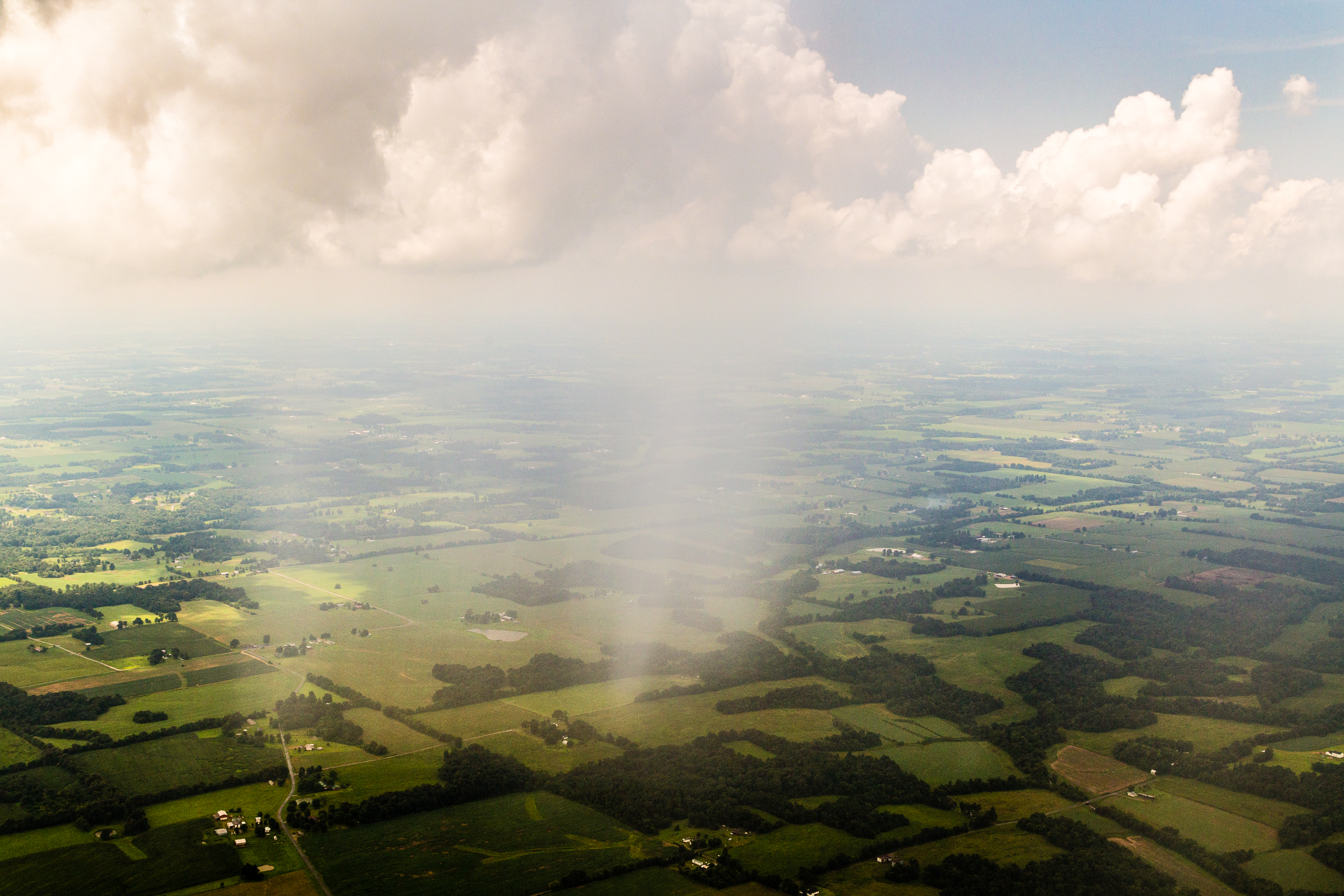 Scattered showers over central Kentucky farmland.