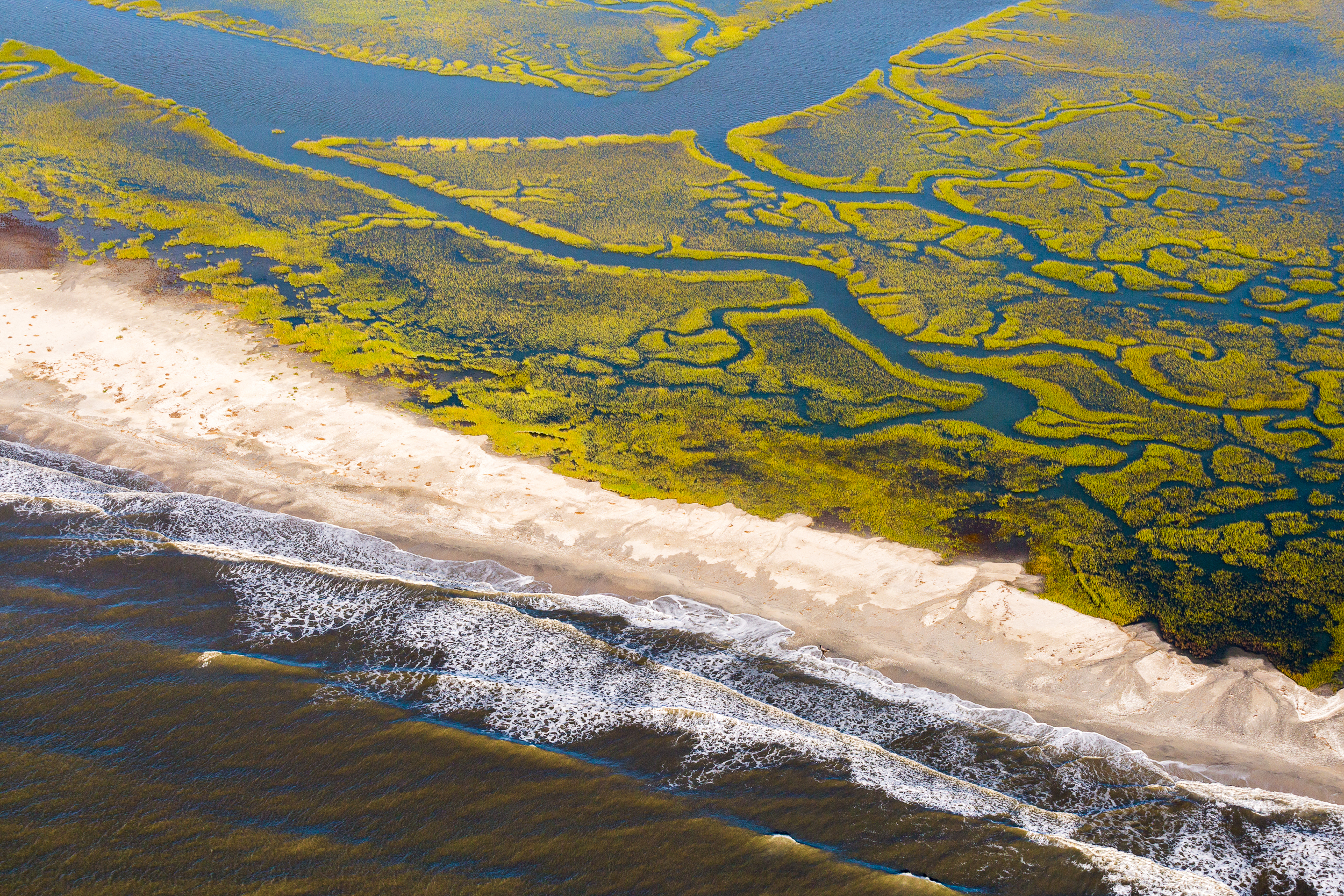 A thin strip of beach separates the Atlantic Ocean from tidal wetlands along the South Carolina coast.