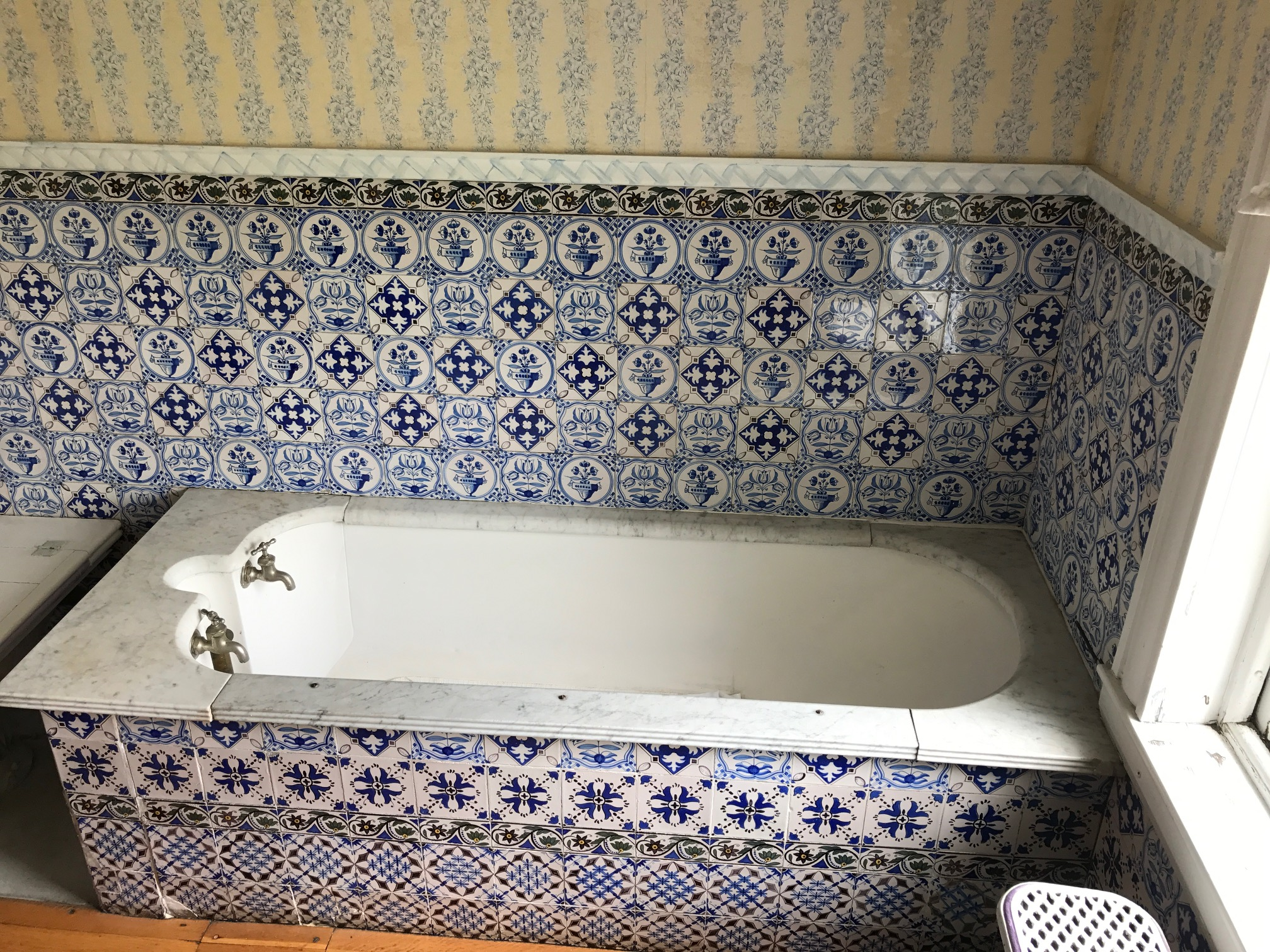 "BEFORE: BEAUTIFULLY DETAILED MOROCCAN & DELFT TILES THAT INSPIRED THE ""RHAPSODY IN BLUES"" THEME. THE OLD BATH TUB WAS FOUND TO BE MADE OF GLEAMING COPPER, WHICH WE RECOVERED."