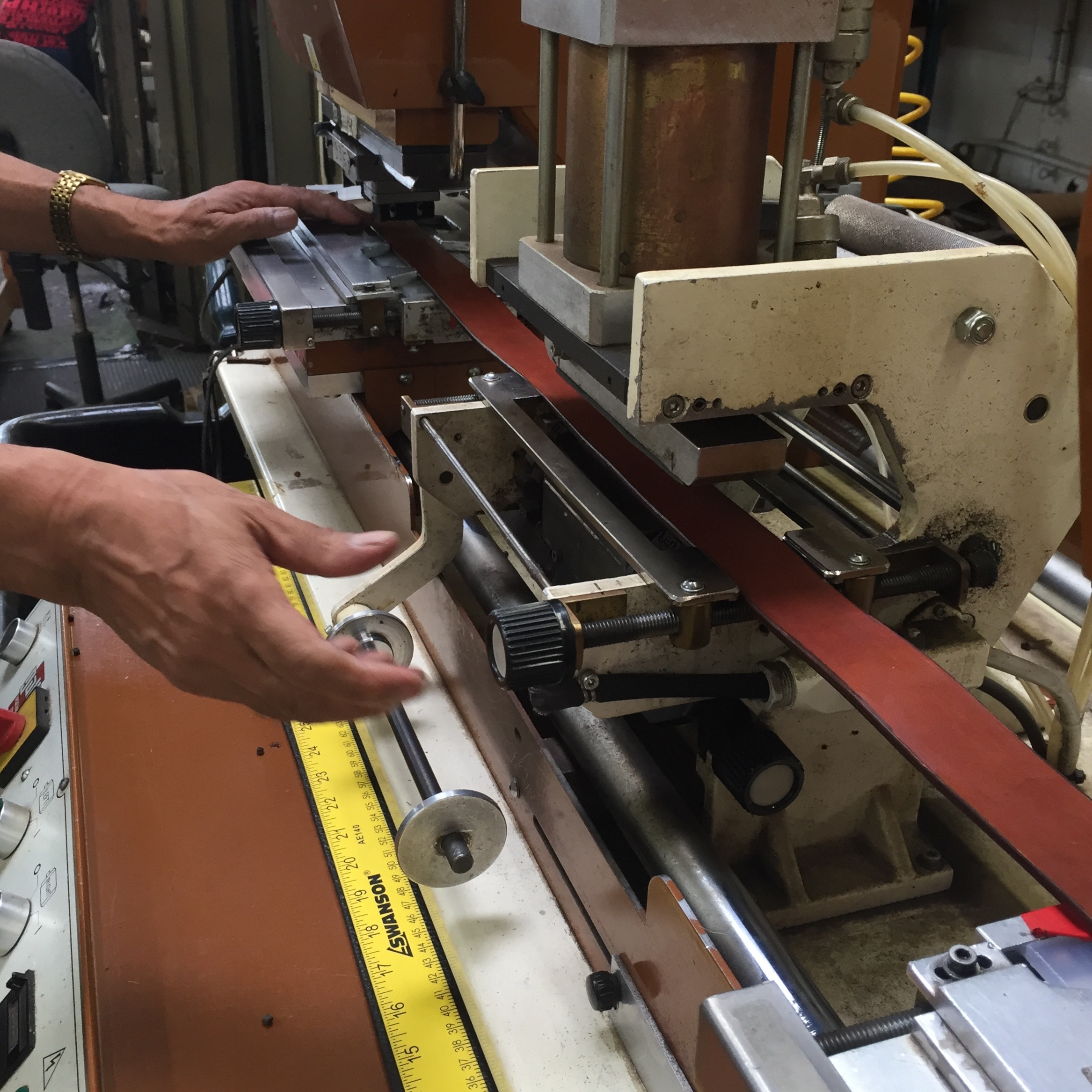 5. The belt is placed in a machine that will punch all holes and emboss the branding. This fellow set the measurements and then I did the punching — woo!