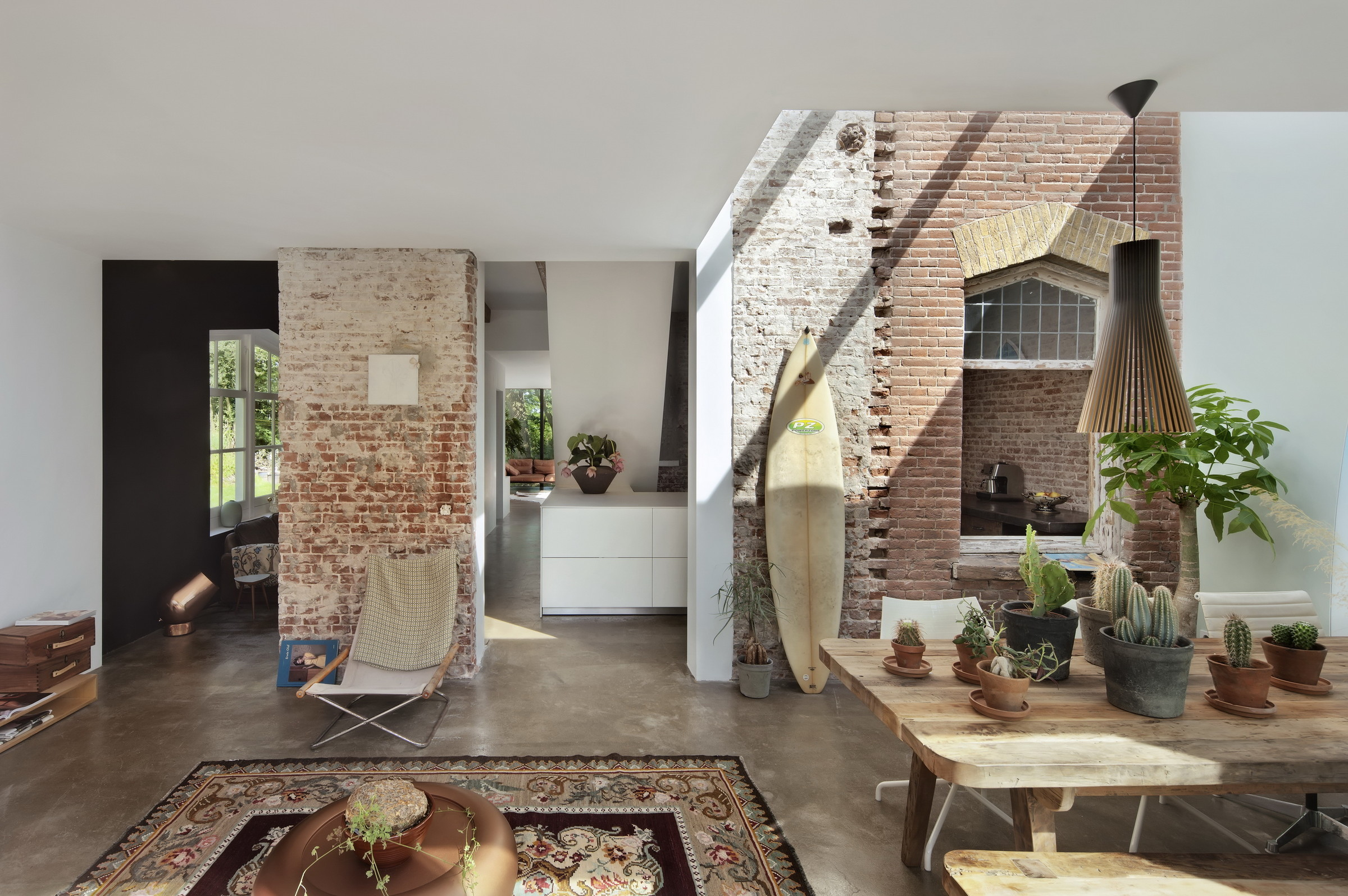 An old railway cottage in Santpoort, The Netherlands by  Zecc Architecture  is flooded with light and maintains its industrial edge. A sunbleached board basks in some rays.