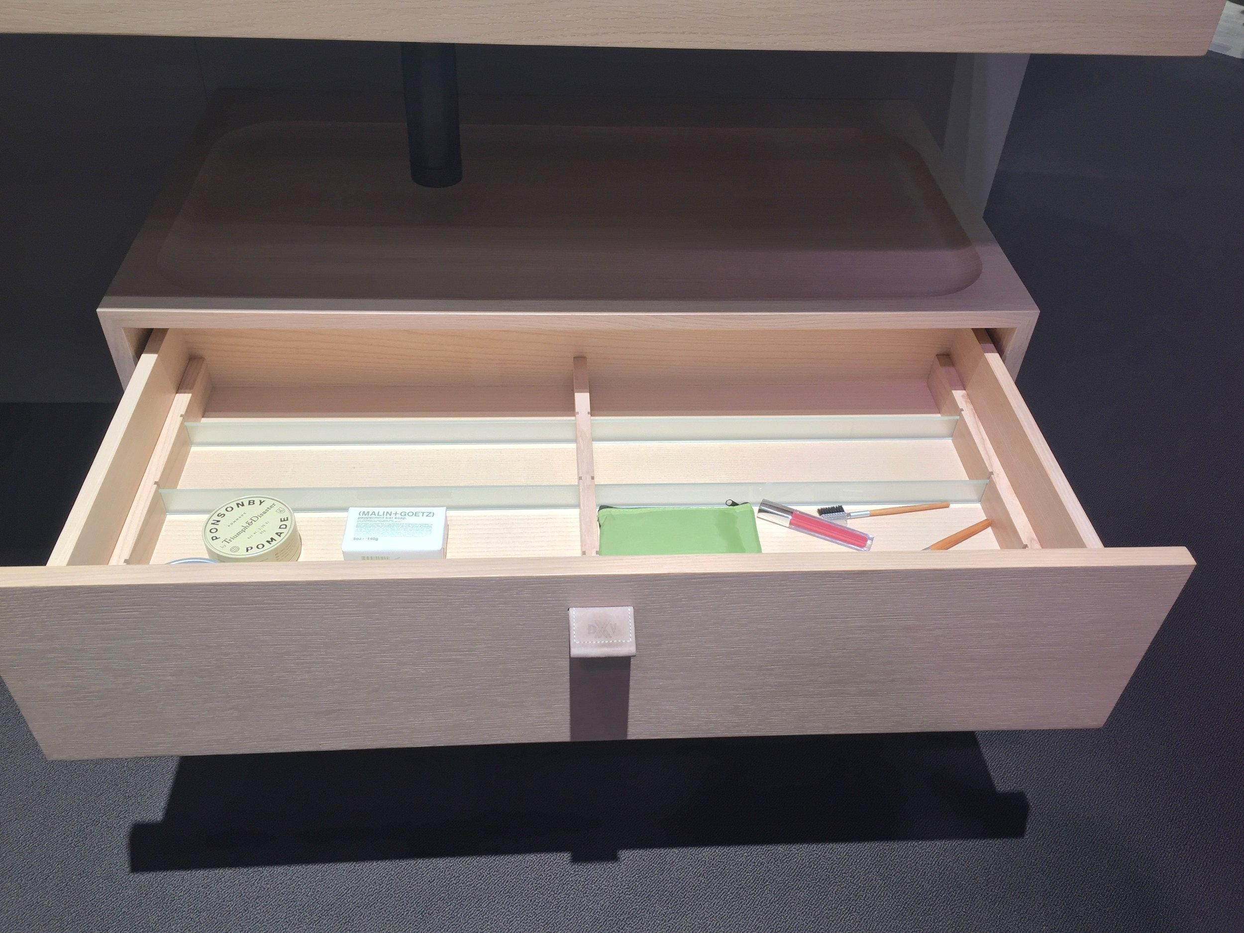 When not in use, the tray from the sink can nestle right on top of the wall-mounted drawer, which is kitted out with clever storage compartments.