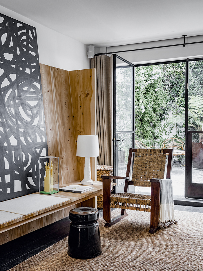 Large artwork in the main living area is by Christian Astuguevieille. Lamp and tabouret are by the designers. The gorgeous rope and wood chair is a flea market find.