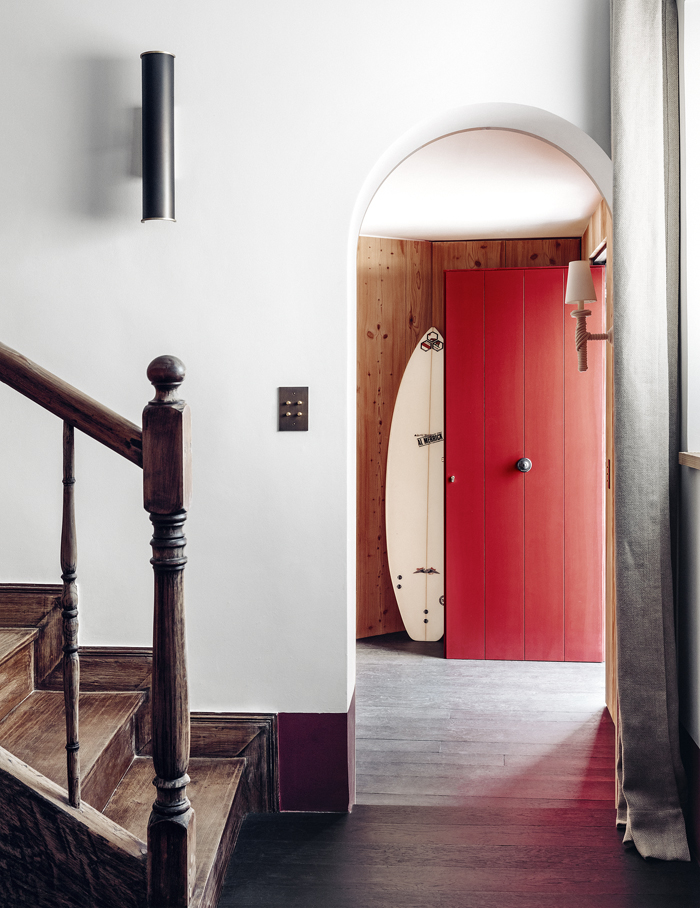 Inside a surfboard is ready to rock when the surf's up. The staircase is original to the house. The sconce it by Gilles & Boissier