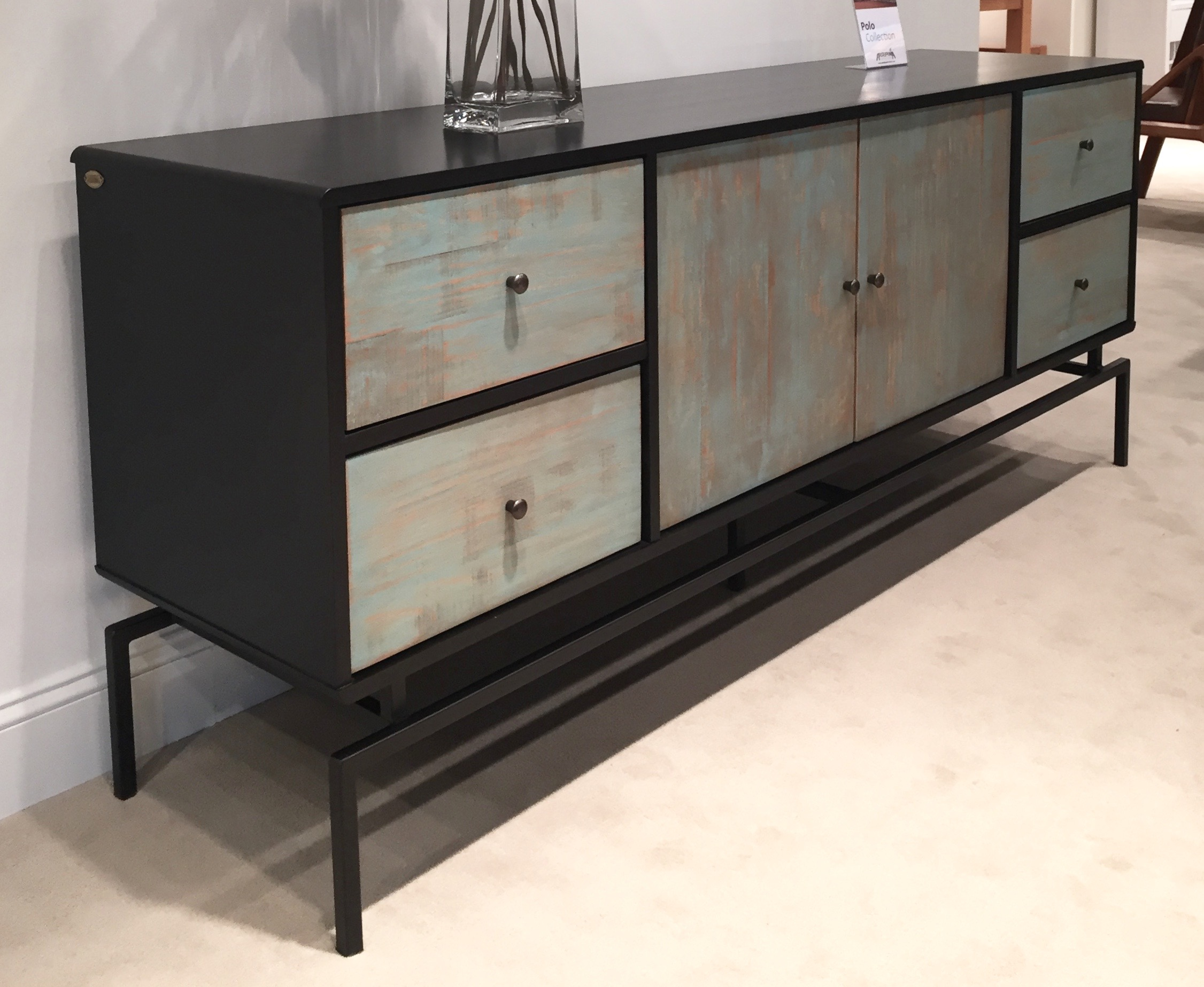 I'd spec this piece in all black instead of that contrasting front — but at a trade show you've got to take every advantage to show what your skilled workers can do. I love a case piece that's light on its feet. The base totally makes this one.