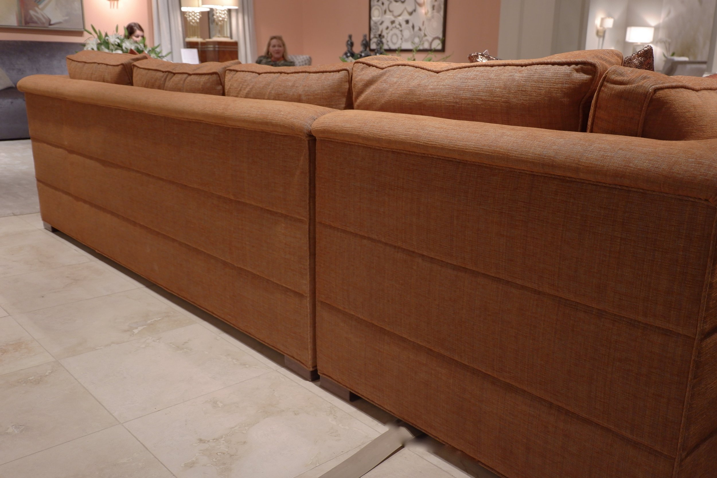 A sofa (in a soft shade of persimmon, no?) with channel detail along the back. Jamie Drake for Theodore Alexander.