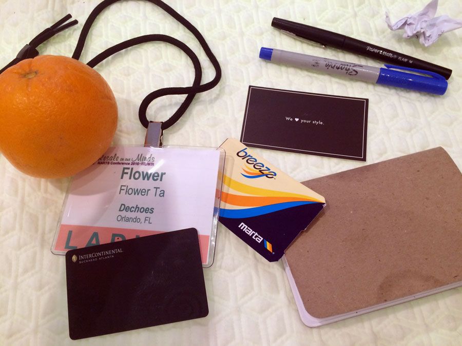 "What's in my go-green-eco-bag?   (from right to left)  1.  An orange from the hotel lounge for energy.  2.  NARTS name badge that was instructed to be worn at all events. No questions.  3.  Intercontinental room key.  4.  MARTA public transit pass.  5.  ""We <3 your style"" card.  6.  Paper Mate Flair - my most favorite pen in the world. My friend from LA sent me a box of 12 for my birthday and now I'm down to only four pens.  7.  Sharpie - standard pen at every Dechoes location. I use blue for writing notes on my arm.  8 . Scout Book - My friend from Portland sent this to me on my birthday. They're compact, light and perfect for jotting down ideas. When I'm juggling things and on the go, I put it in my mouth. You can see my lip print on the edge of both sides.."
