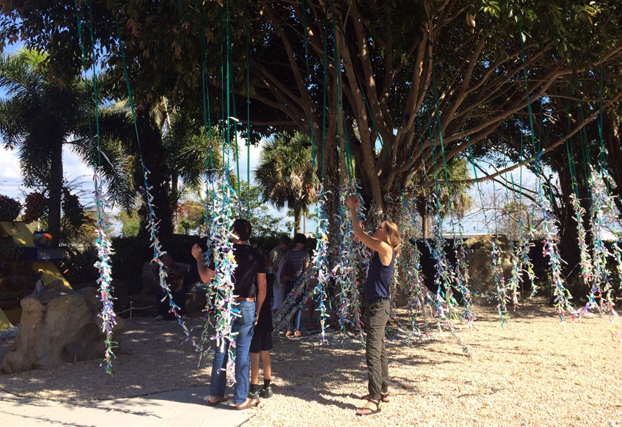 Wishful thinking.  Juli and other visitors add wishes to the ficus tree outside the museum.