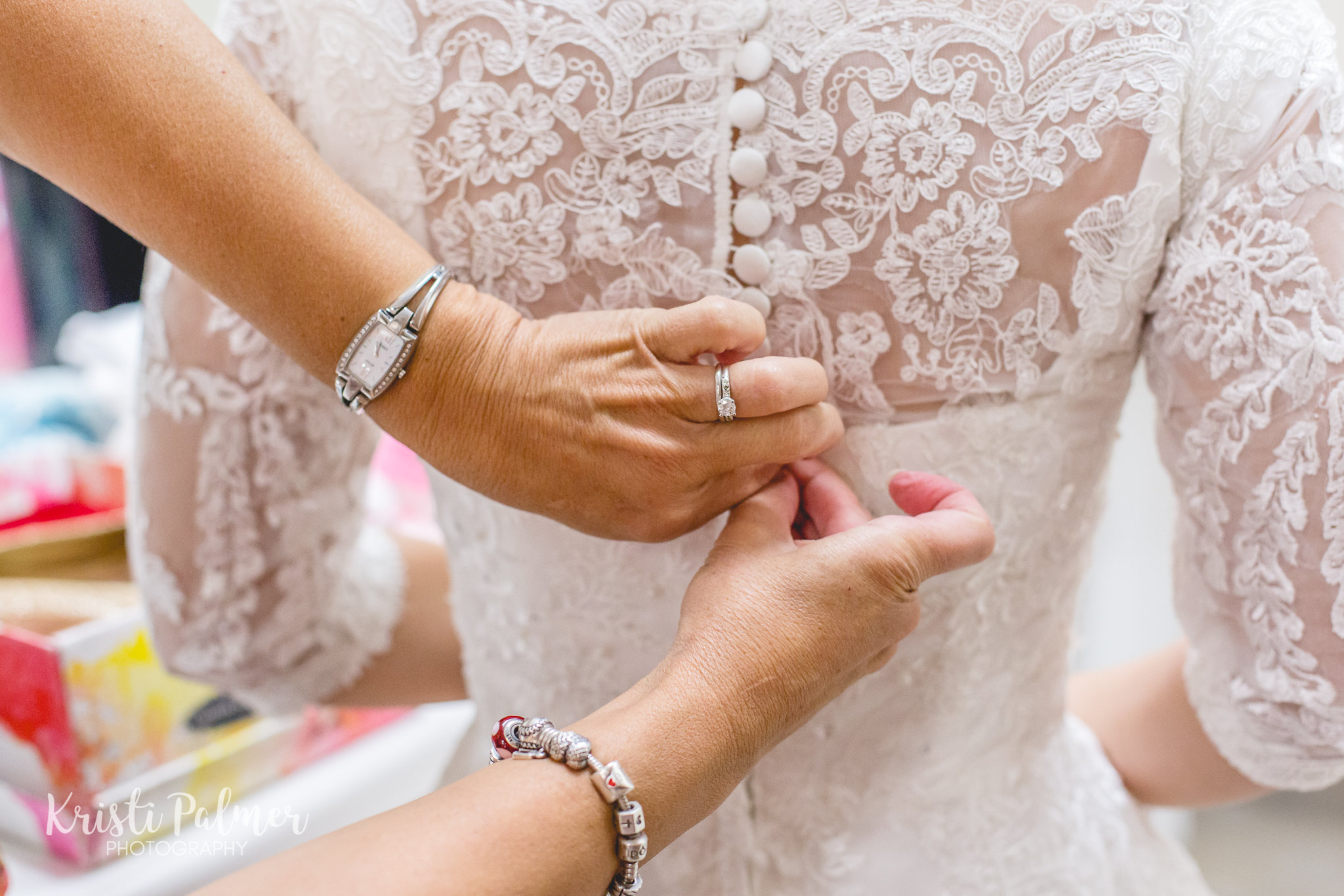 bride's mother helping her into wedding dress