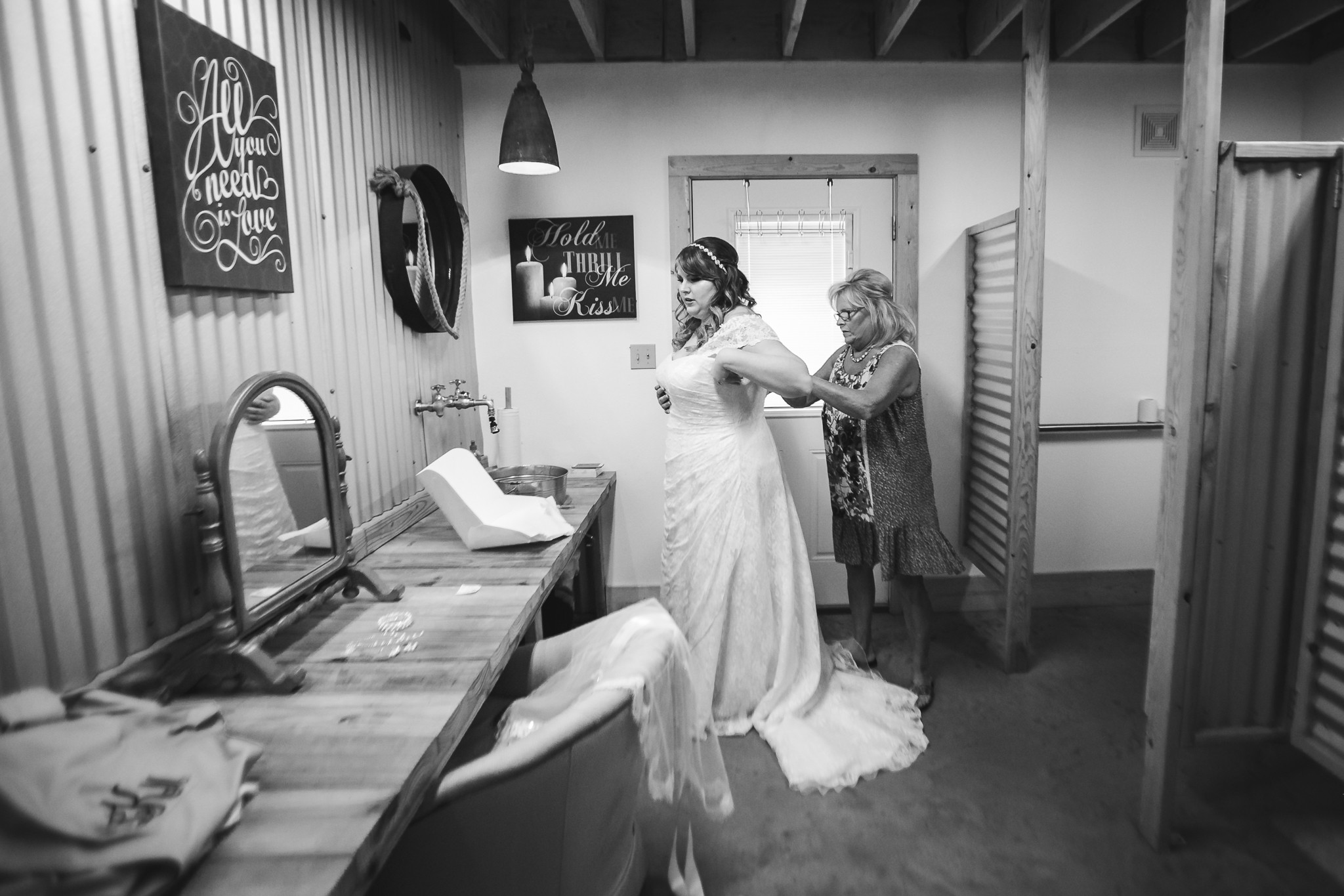 bride's mom helping her into her wedding dress