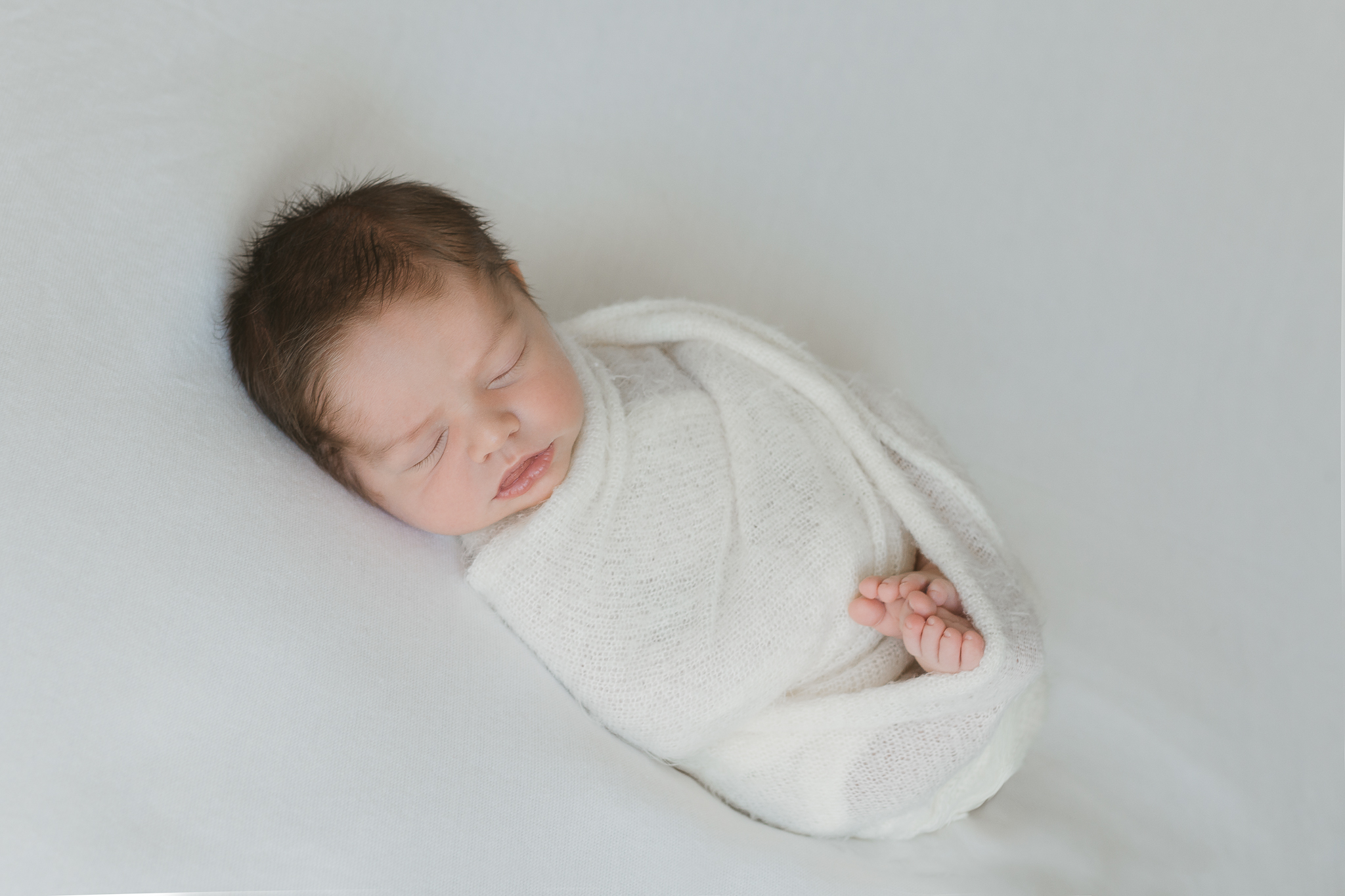 baby wrapped in white on natural white background