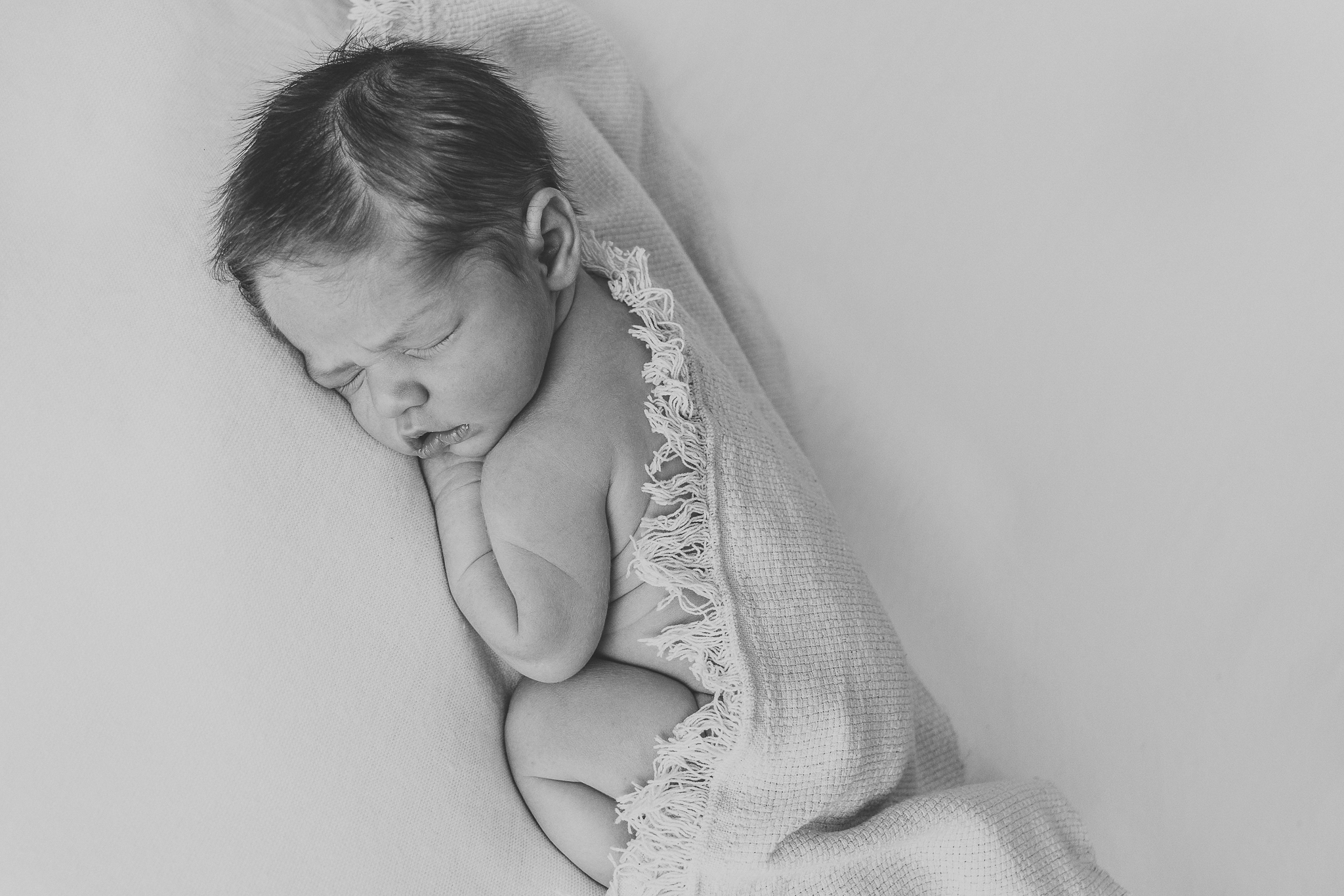 sound asleep newborn baby with fringed wrap in black and white