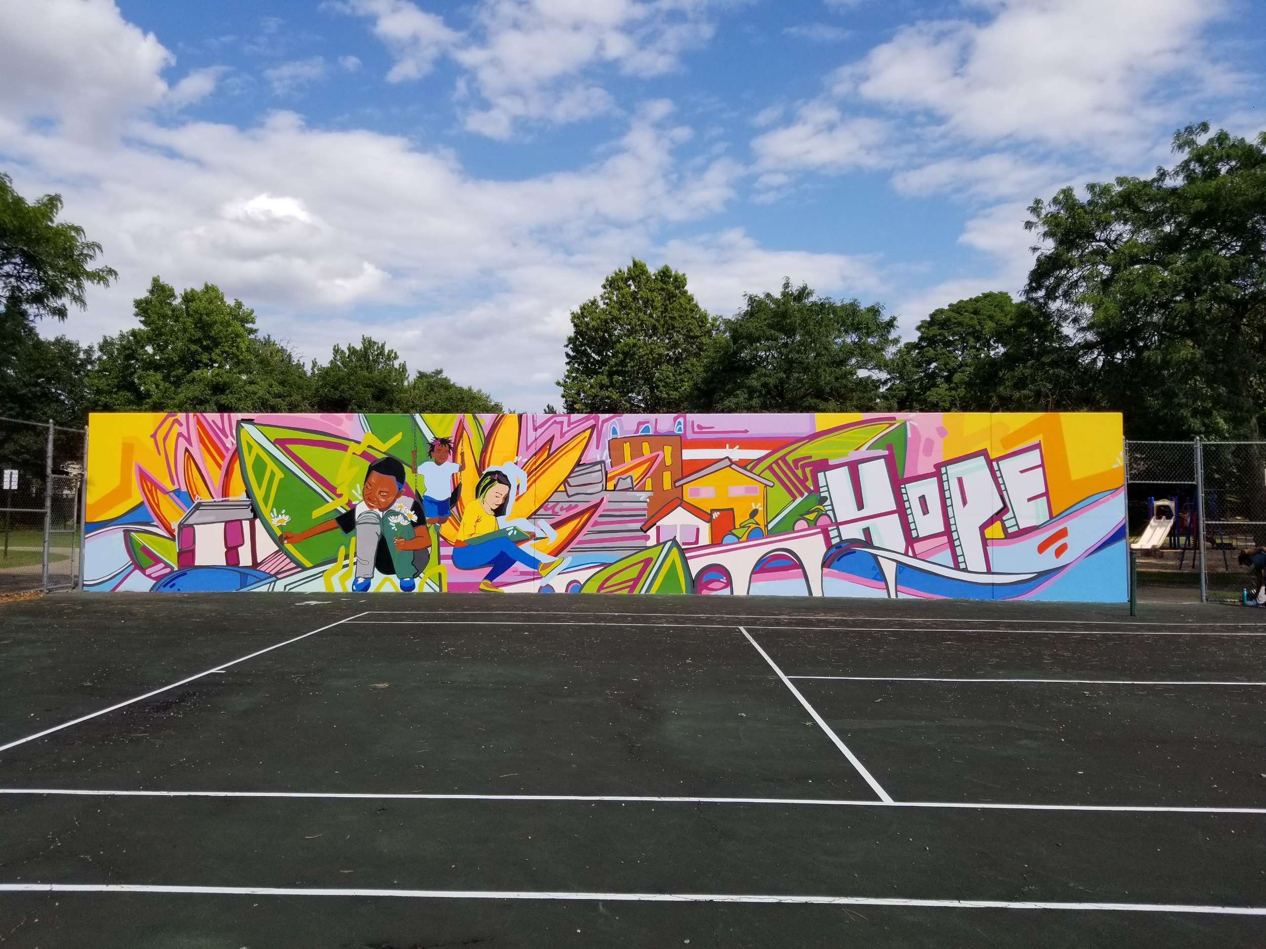 "Park East mural view 1     This mural was developed in collaboration with residents in Akron Ohio whose homes are located adjacent to ""Park East'' just south of downtown. Resident input directed content, colors, themes and imagery in the final mural."