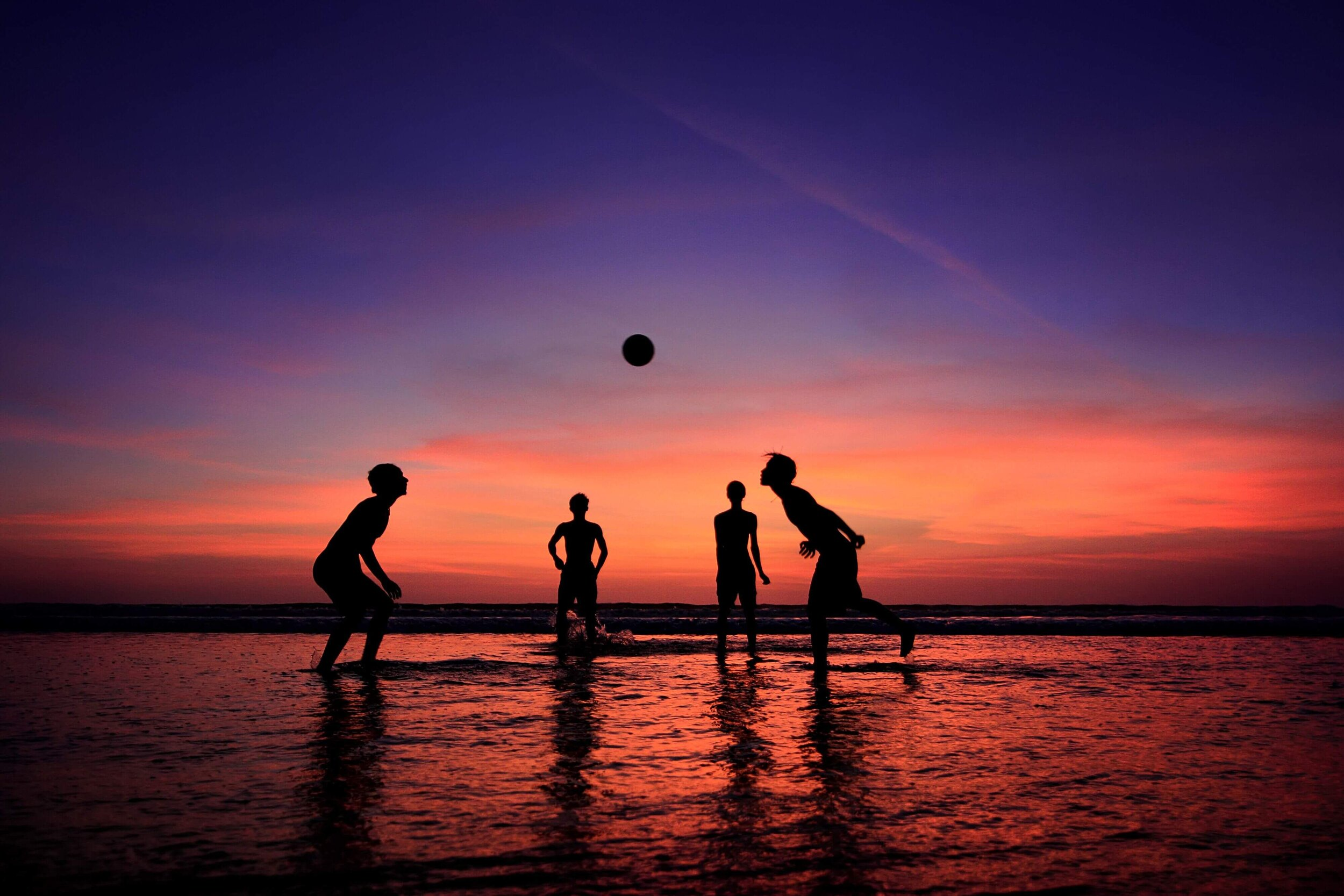 group of locals playing volleyball on a beach at sunset in bali.jpeg