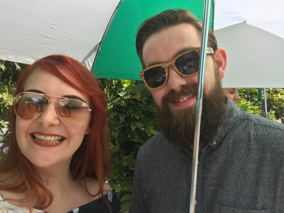 Two overdressed beans hiding under an umbrella from the insane heat!
