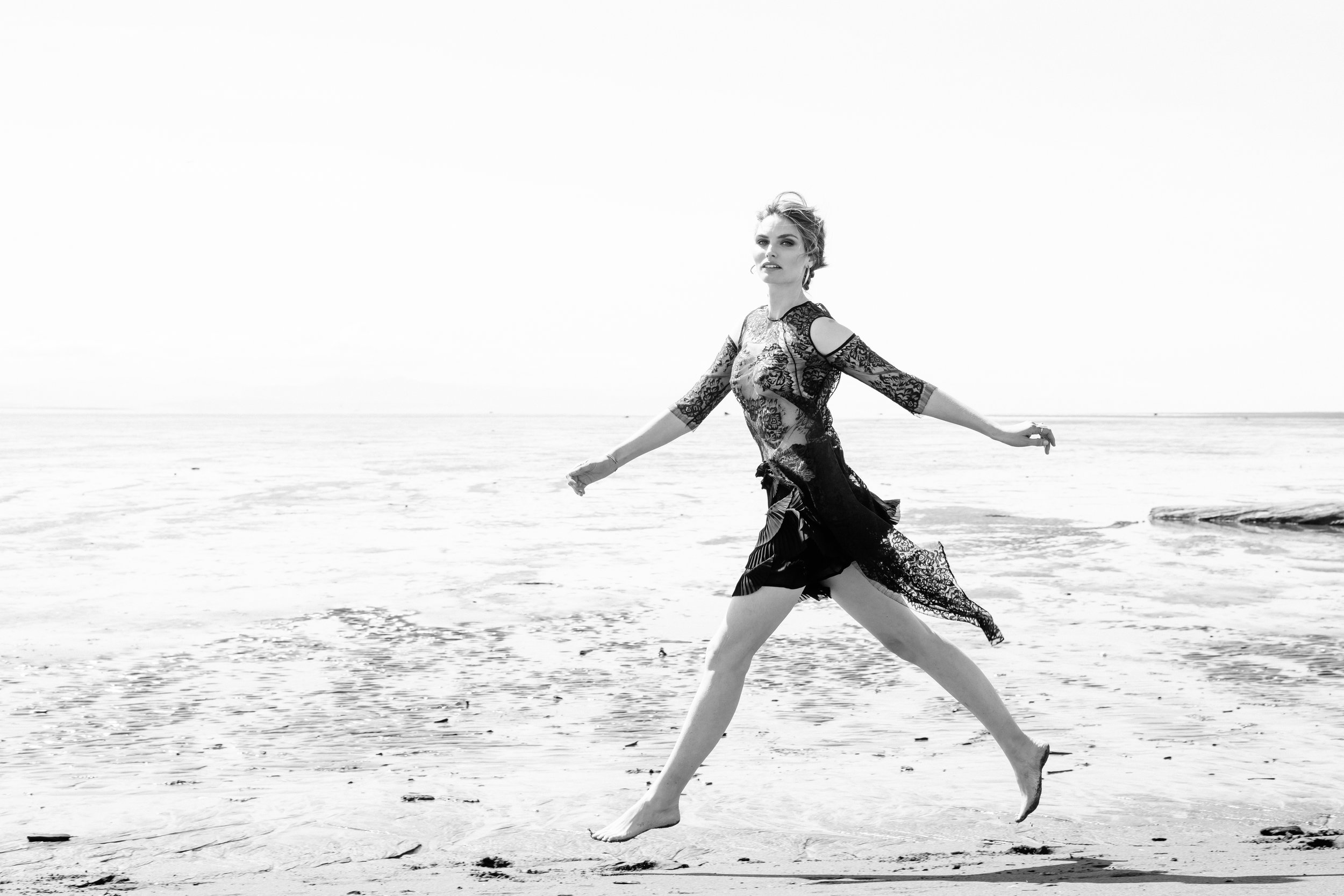 Black and white photo of model running on the beach.