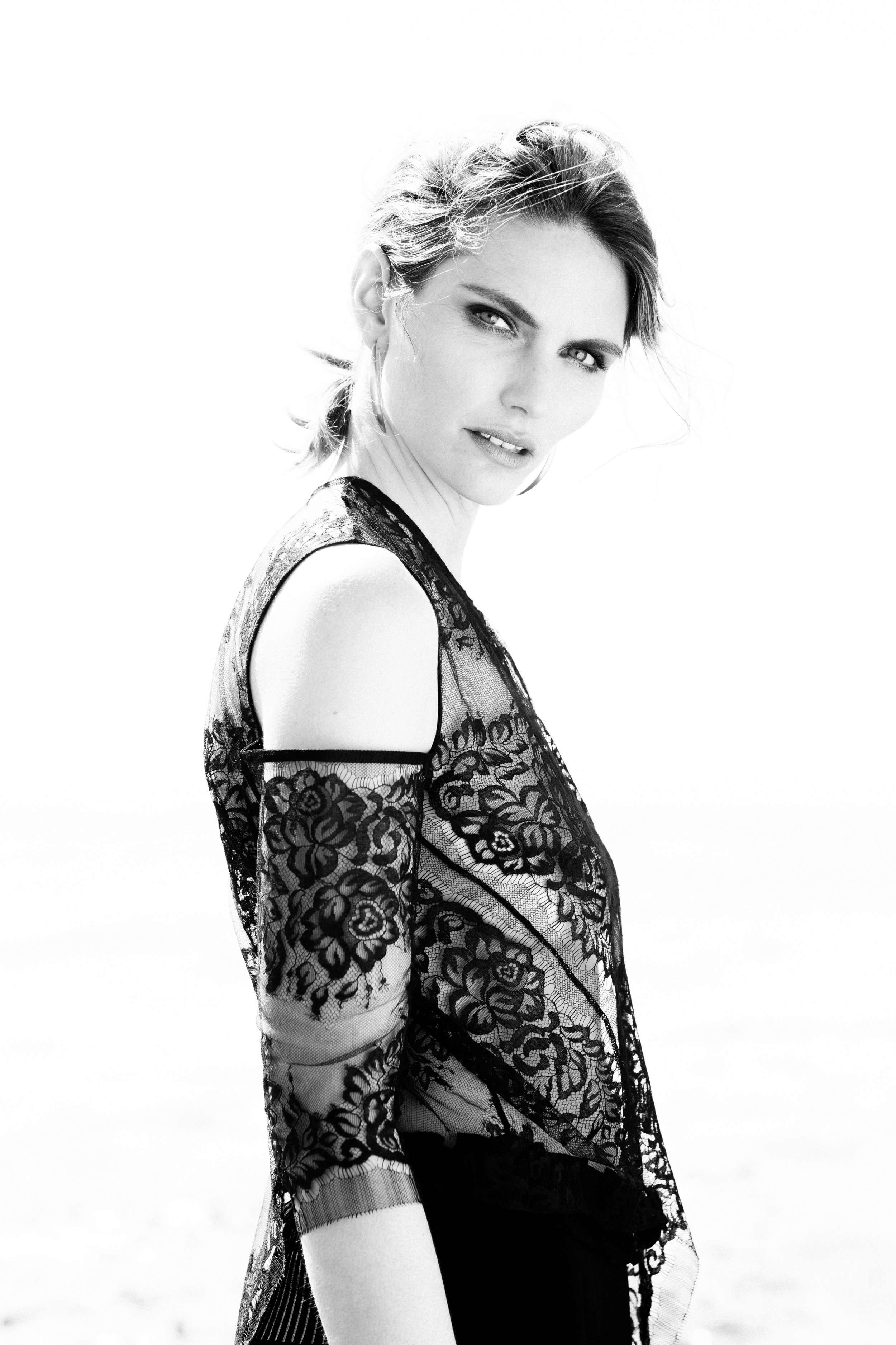 Black and white editorial fashion photo of model wearing black lace dress.