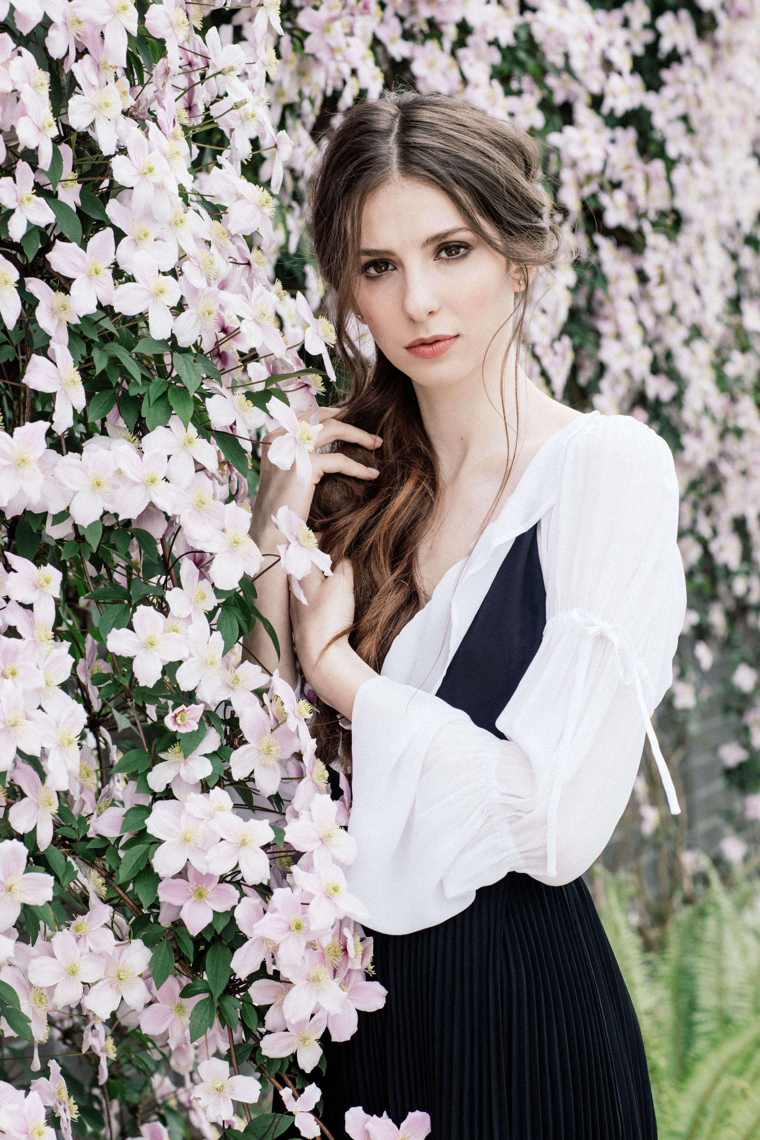 Portrait of Genevieve Buechner in a white shirt and black dress posing by a flower bush.