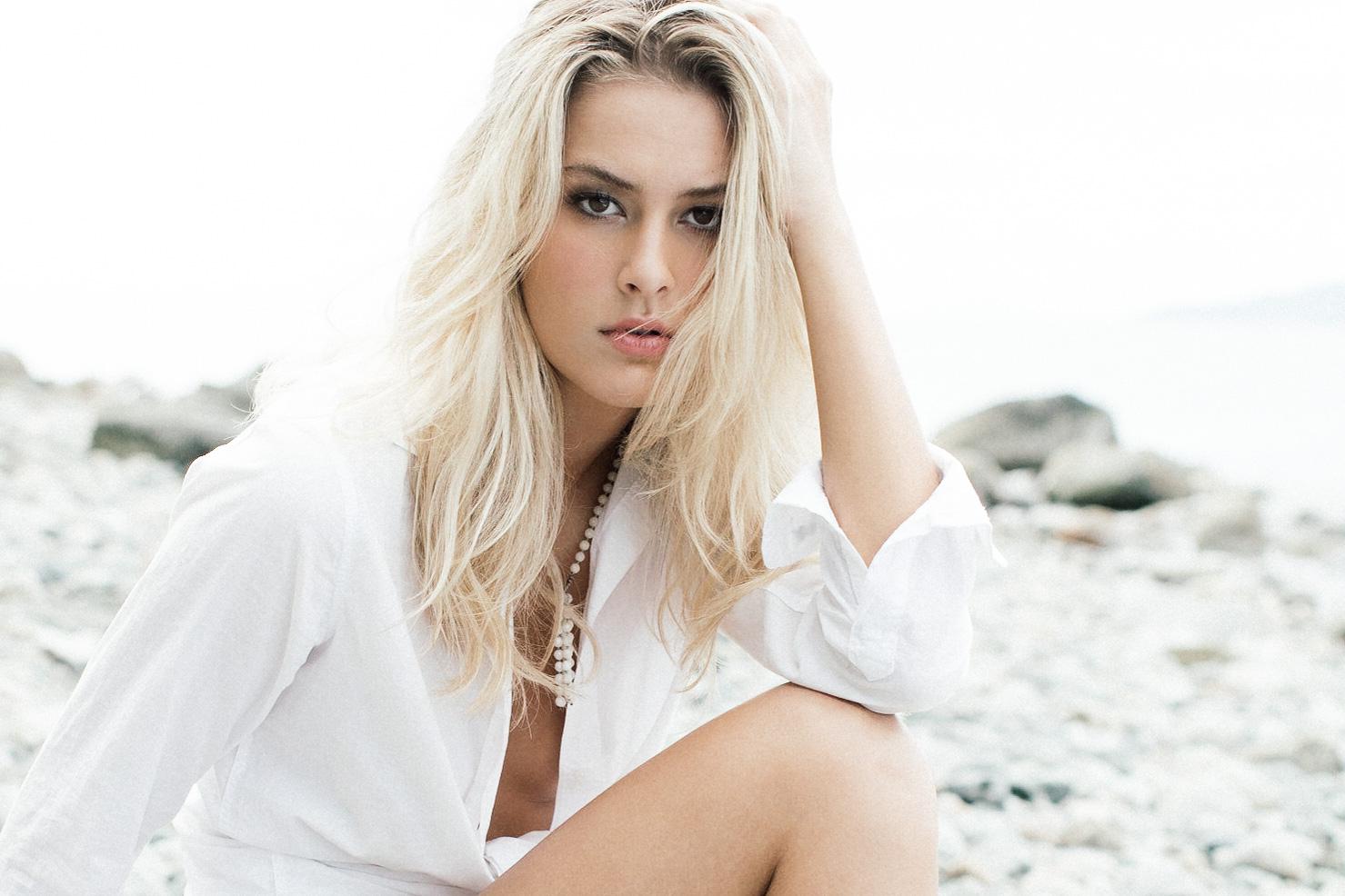 Model Corinne Isherwood on the beach in a white shirt.