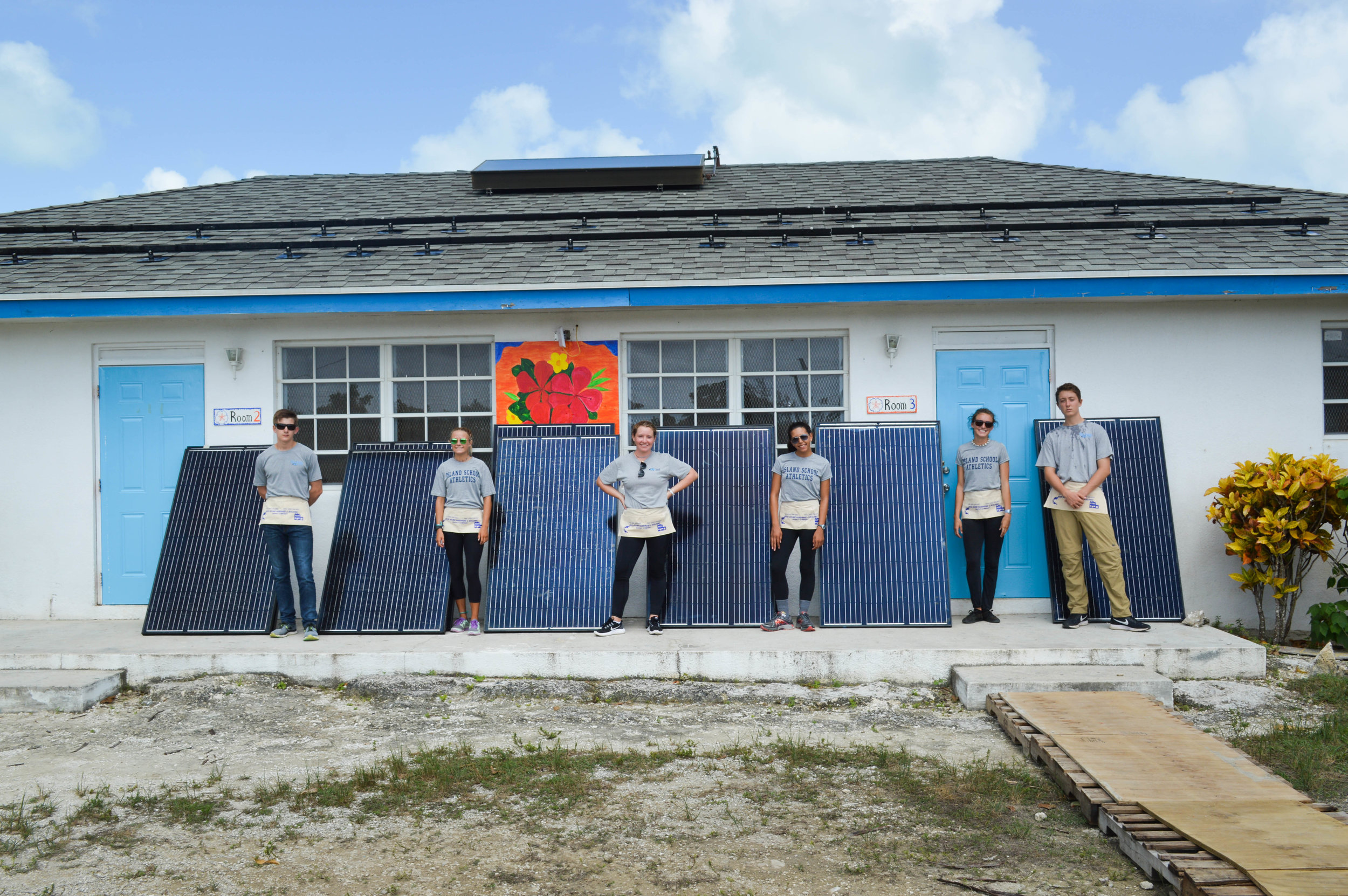 Island School students stand with the solar PV modules before they helped to install them.