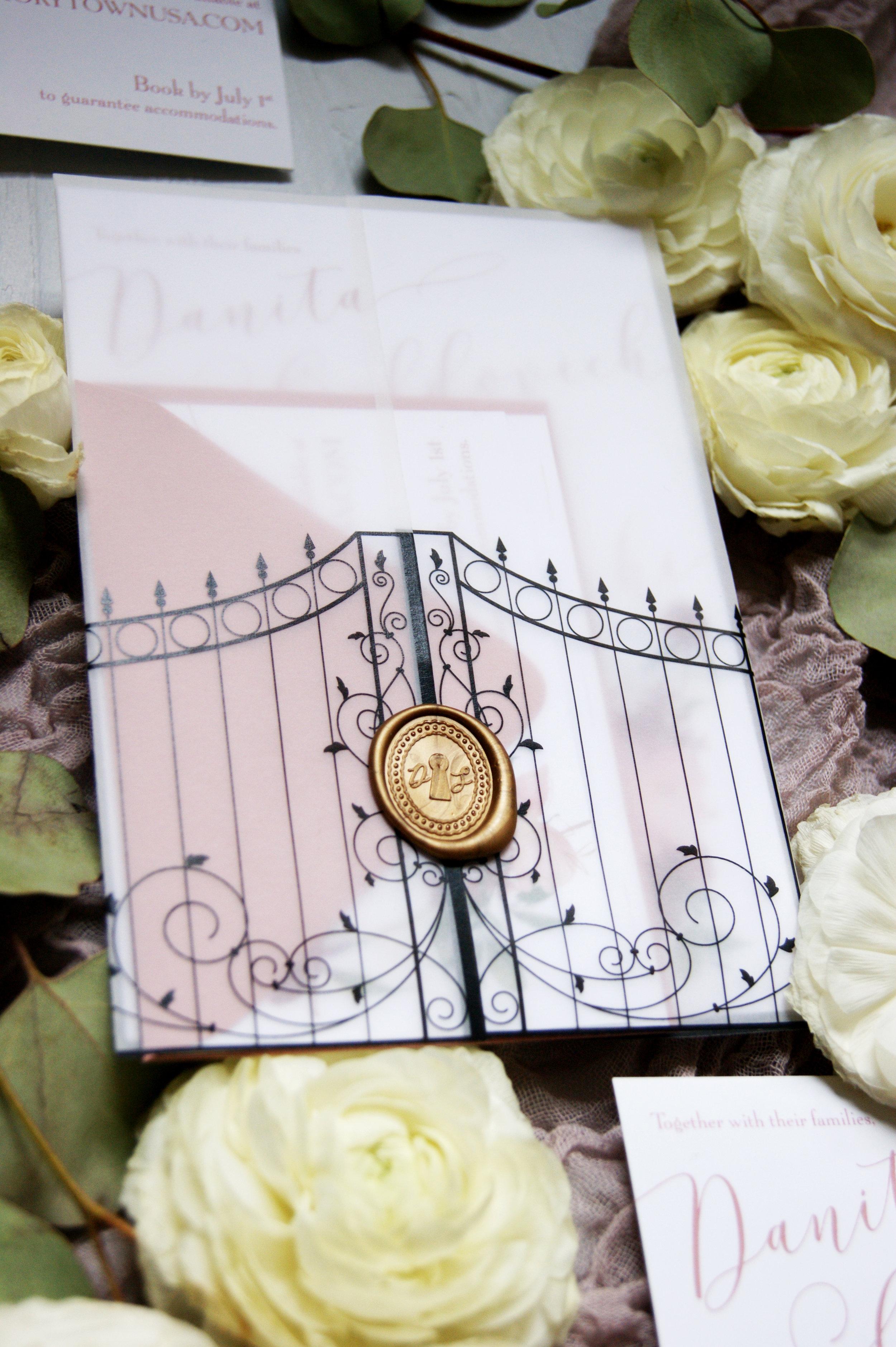 Vellum wrapped wedding invitation with custom gold wax seal.
