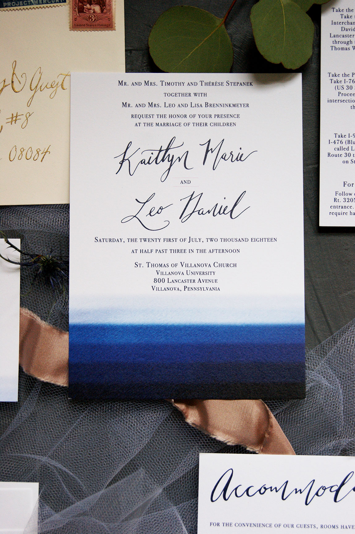 Navy watercolor wedding invitation with custom calligraphy and blush accents.