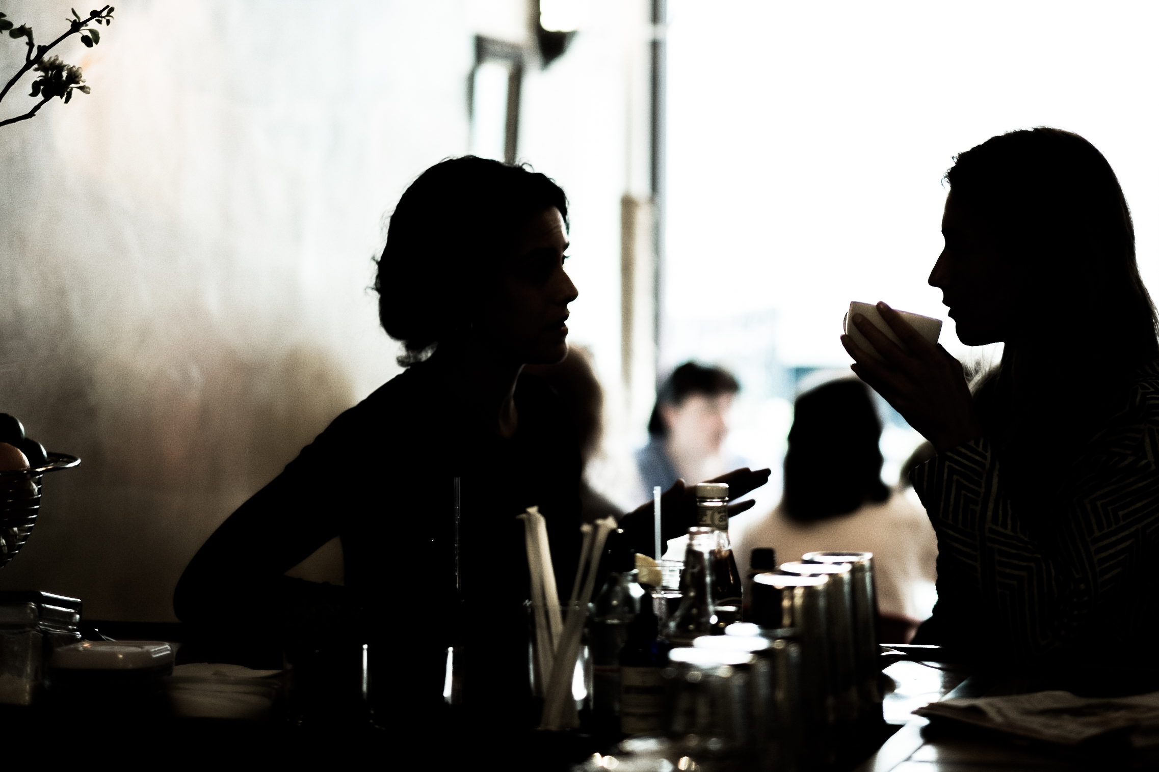 Silhouette of two people chatting at the bar