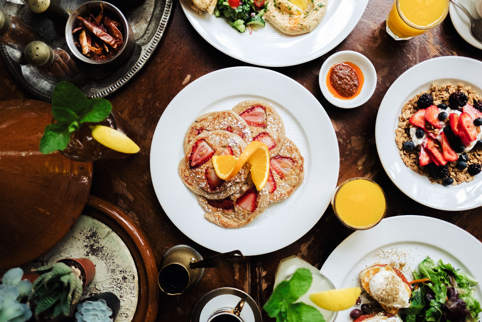 Breakfast spread, pancakes, granola, halloumi eggs, harissa, orange juice