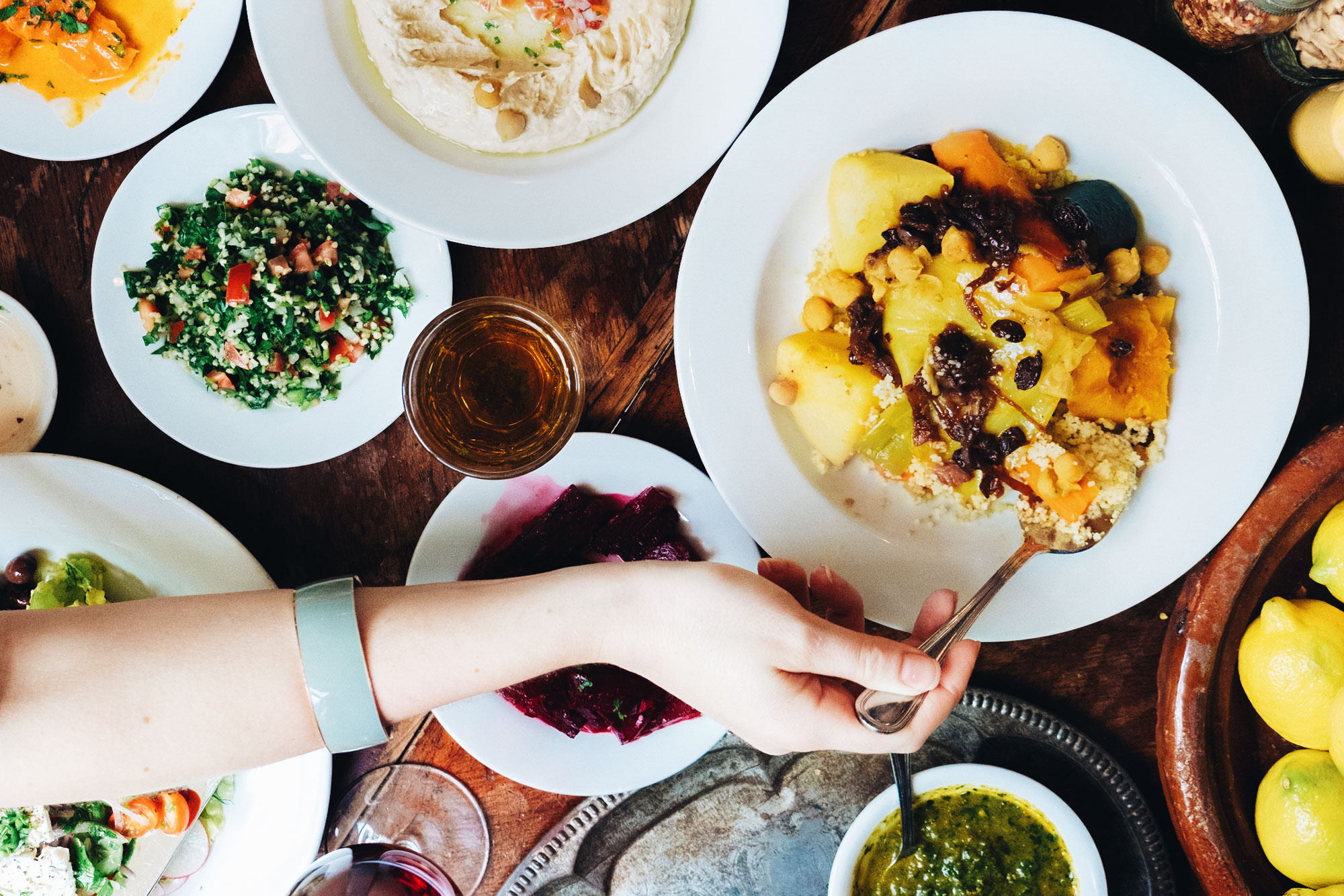 A womans hand reaching for the vegetable couscous. Hummus platter, tabouli, beets and lemons on the table.