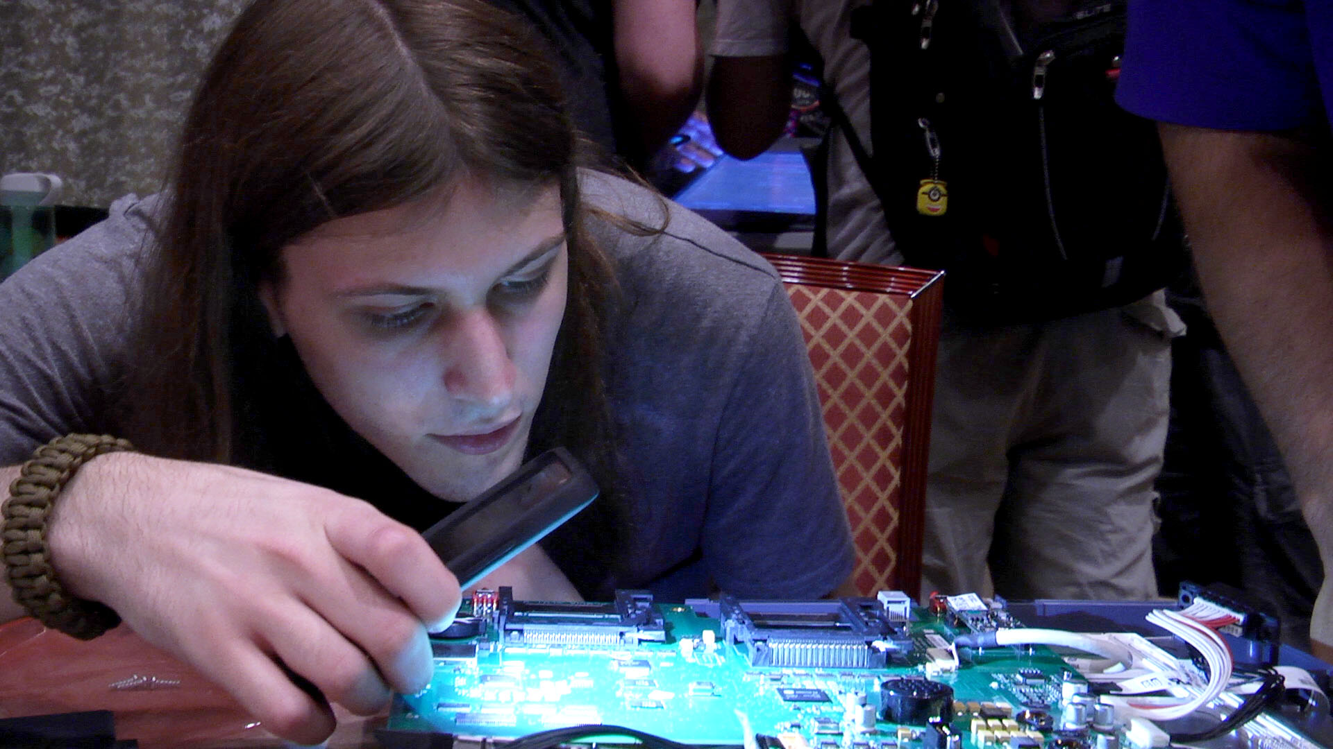 DEF CON 25 Voting Village: Ryan Quasney looks at the board of an AccuVote TSx. Ryan, who is new to hacking estimated he could manipulate votes within two months. He thought an experienced hacker could do it in less than a week.  Photo credit: Lulu Friesdat ©2017