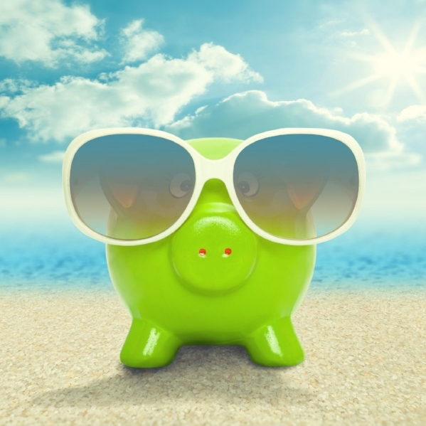 31654537 - piggy bank in sunglasses on the beach - vacation concept