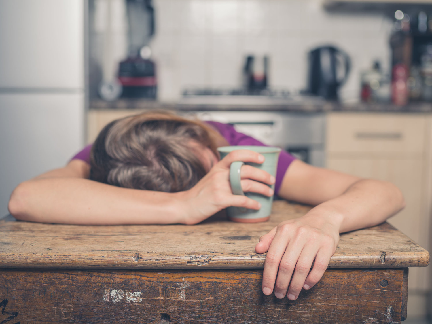 43388665 - a tired young woman is having a cup of tea and is resting her head on a table