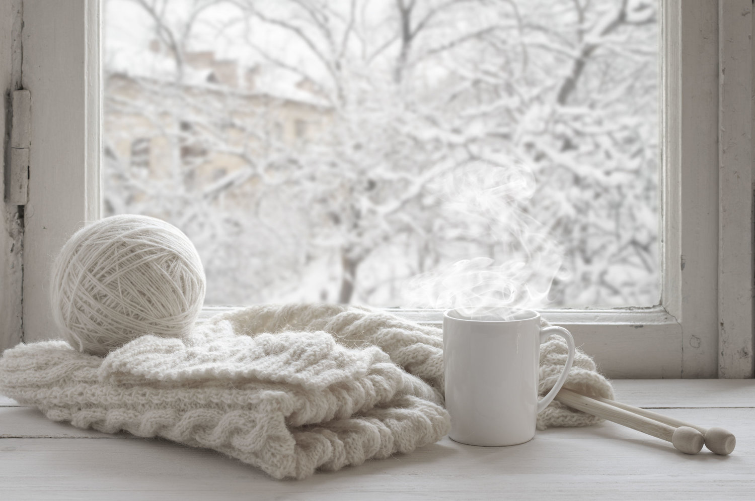 47967113 - cozy winter still life: mug of hot tea and warm woolen knitting on vintage windowsill against snow landscape from outside.
